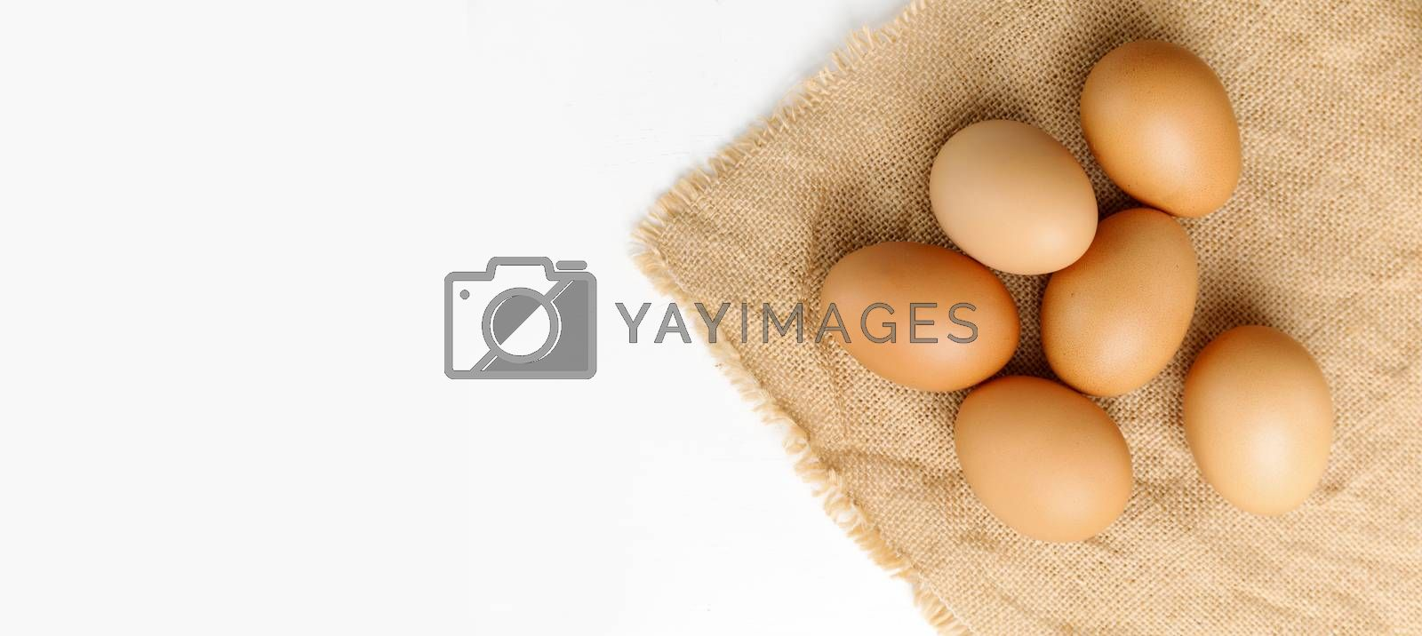 Close up Top view fresh chicken eggs on linen tablecloth with copy space banner.