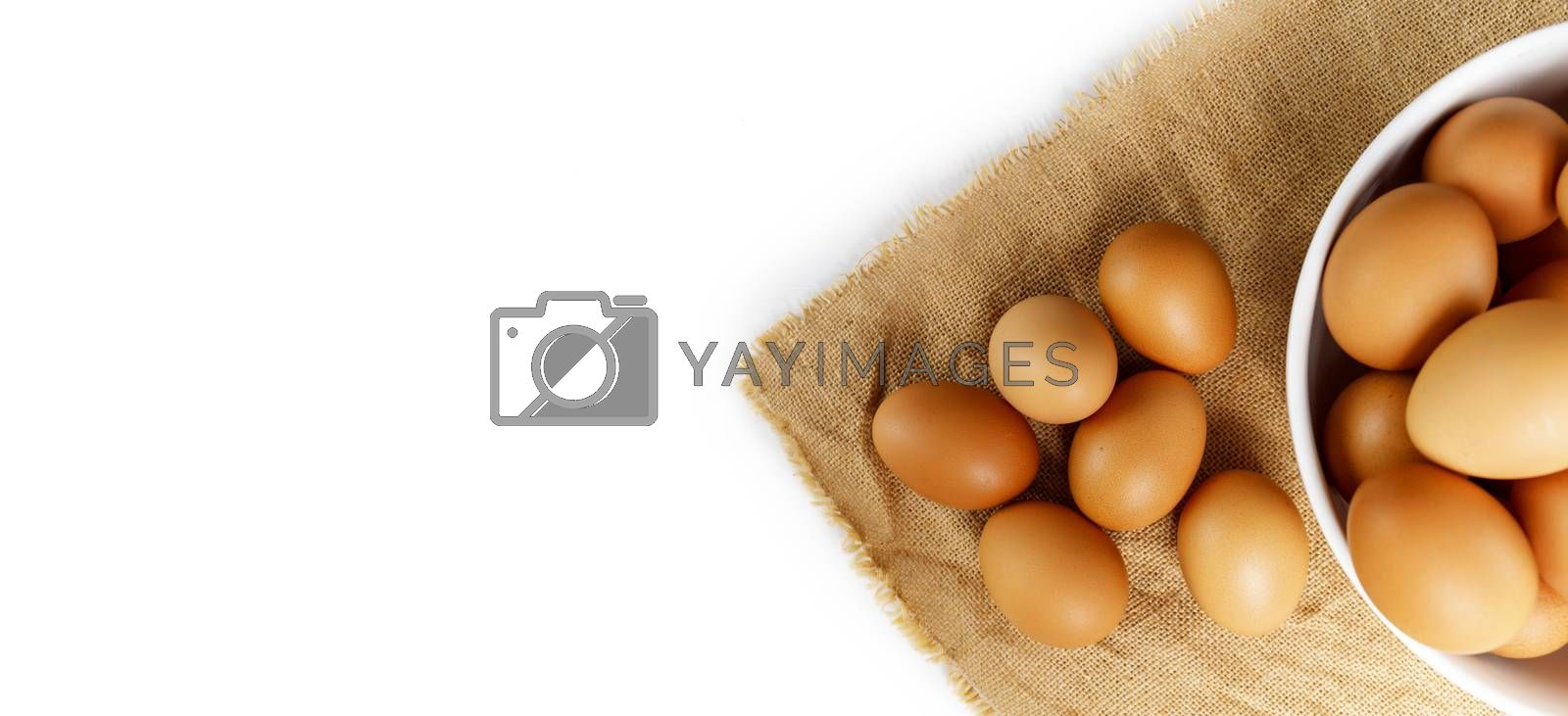 Top view fresh chicken eggs and blur fresh chicken eggs in white bowl on linen tablecloth with copy space banner. Uncooked raw eggs in bowl.
