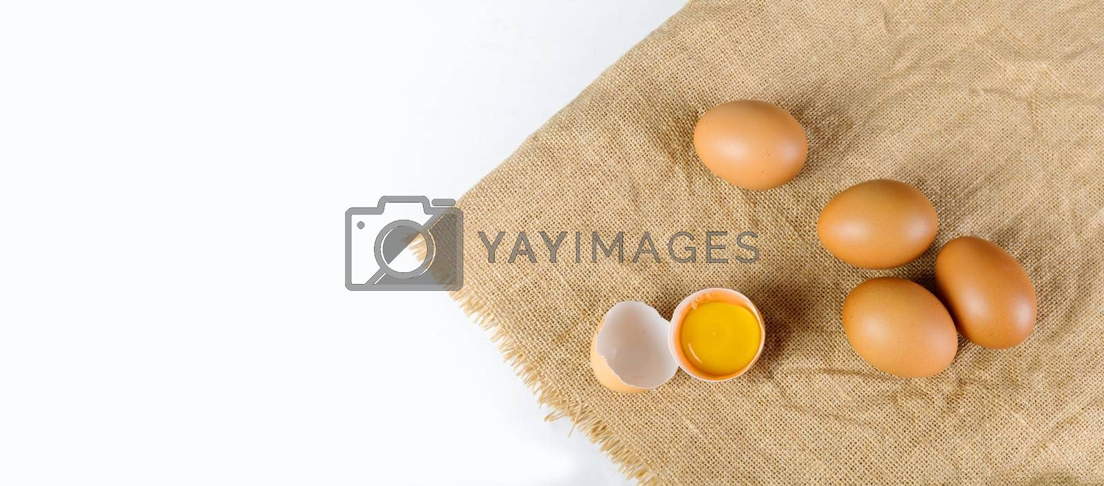 Top view broken raw egg with the yolk and albumen on a linen tablecloth on white background. Raw eggs on white table with copy space banner.