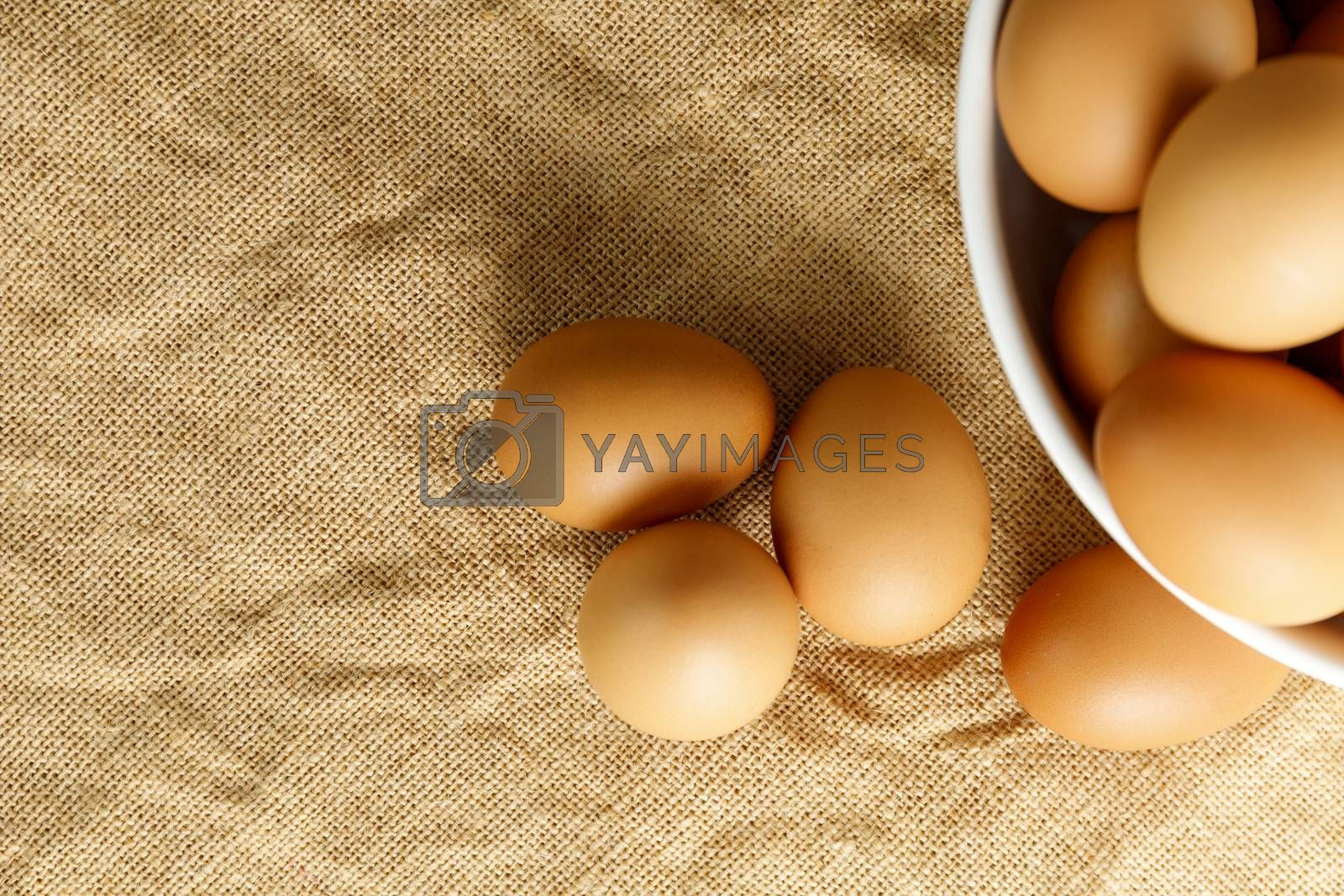 Top view fresh chicken eggs and blur fresh chicken eggs in white bowl on linen tablecloth with copy space. Uncooked raw eggs in bowl.