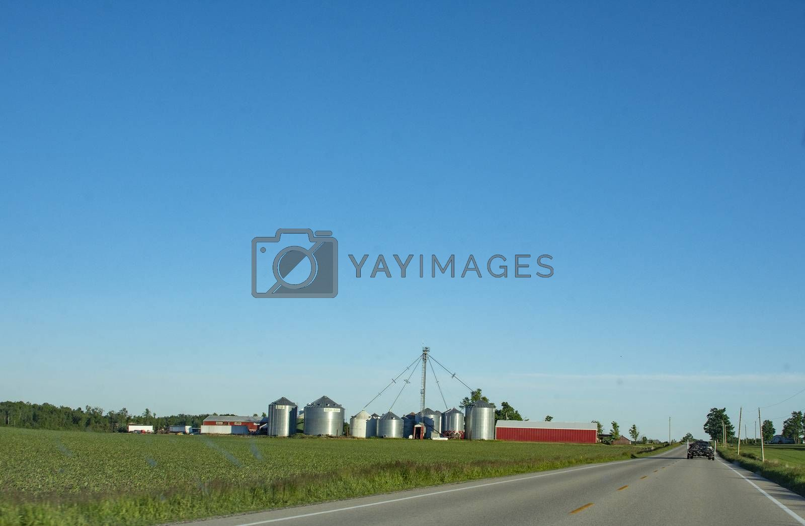 Farm buildings at the end of a large field that stretches along the road