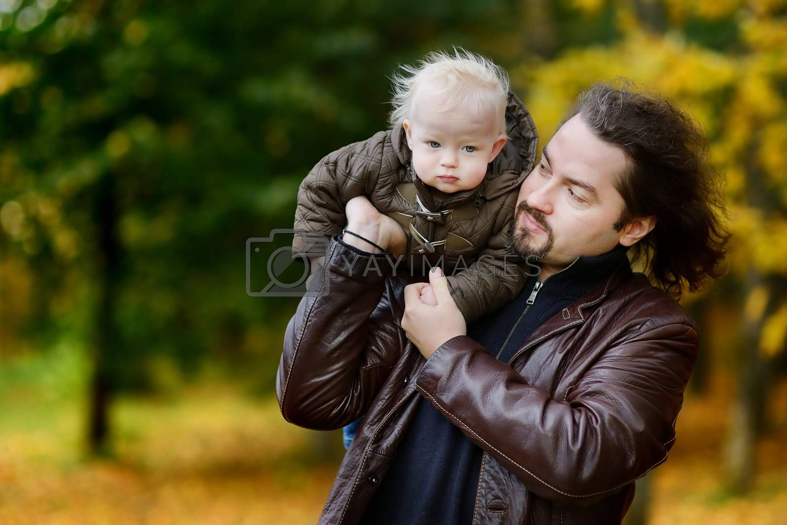 Young father and his toddler daughter at fall