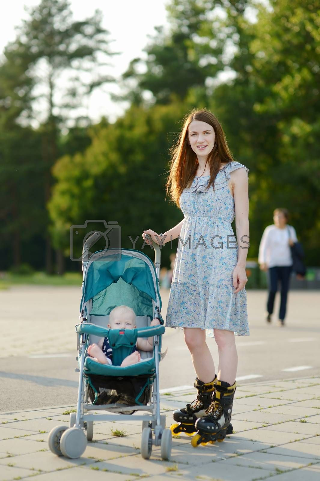 Young mother on roller skates with baby stroller