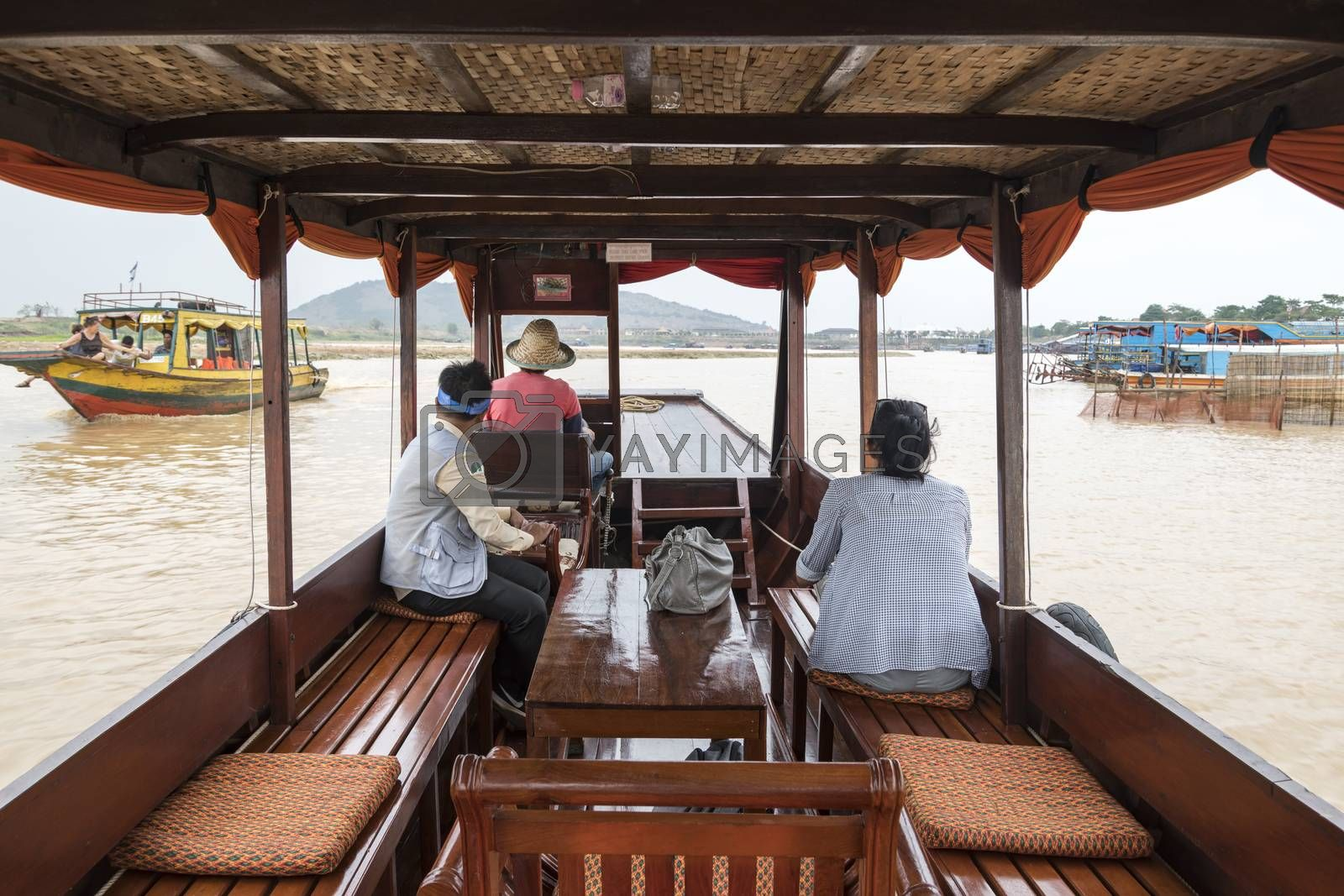 European tourist (lady) on a private cruise tour  with her guide going to visit the a village on the famous Tonle Sap Lake, Siem Reap, Cambodia, Asia