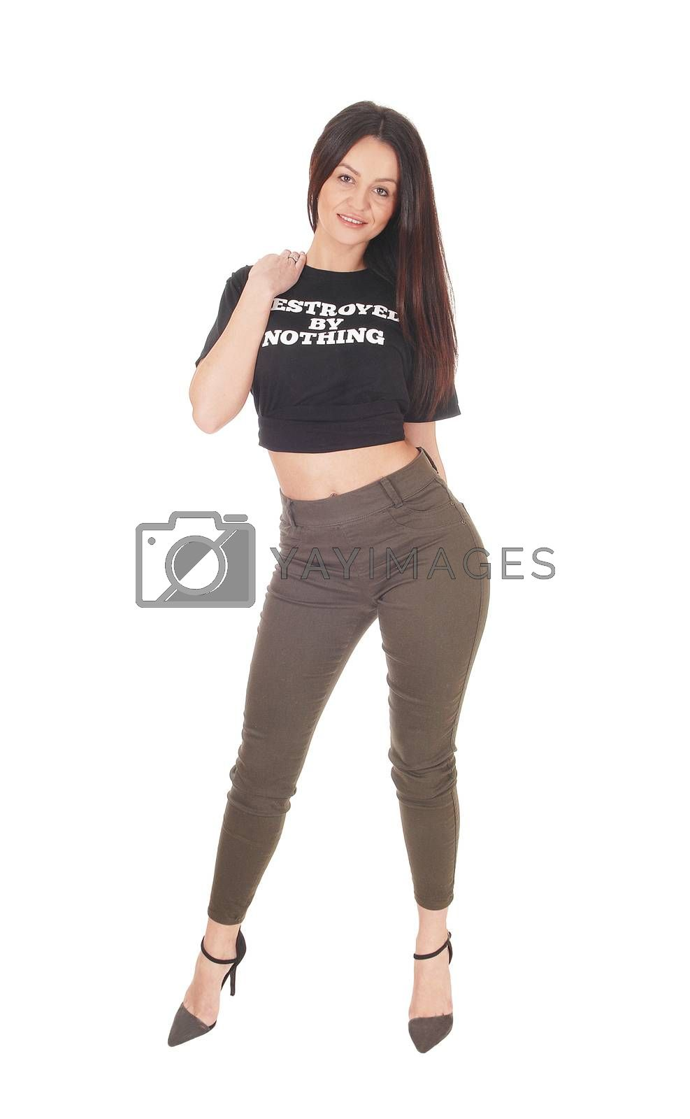 Beautiful slim young woman standing in the studio from the front, looking in the camera and smiling, isolated for white background