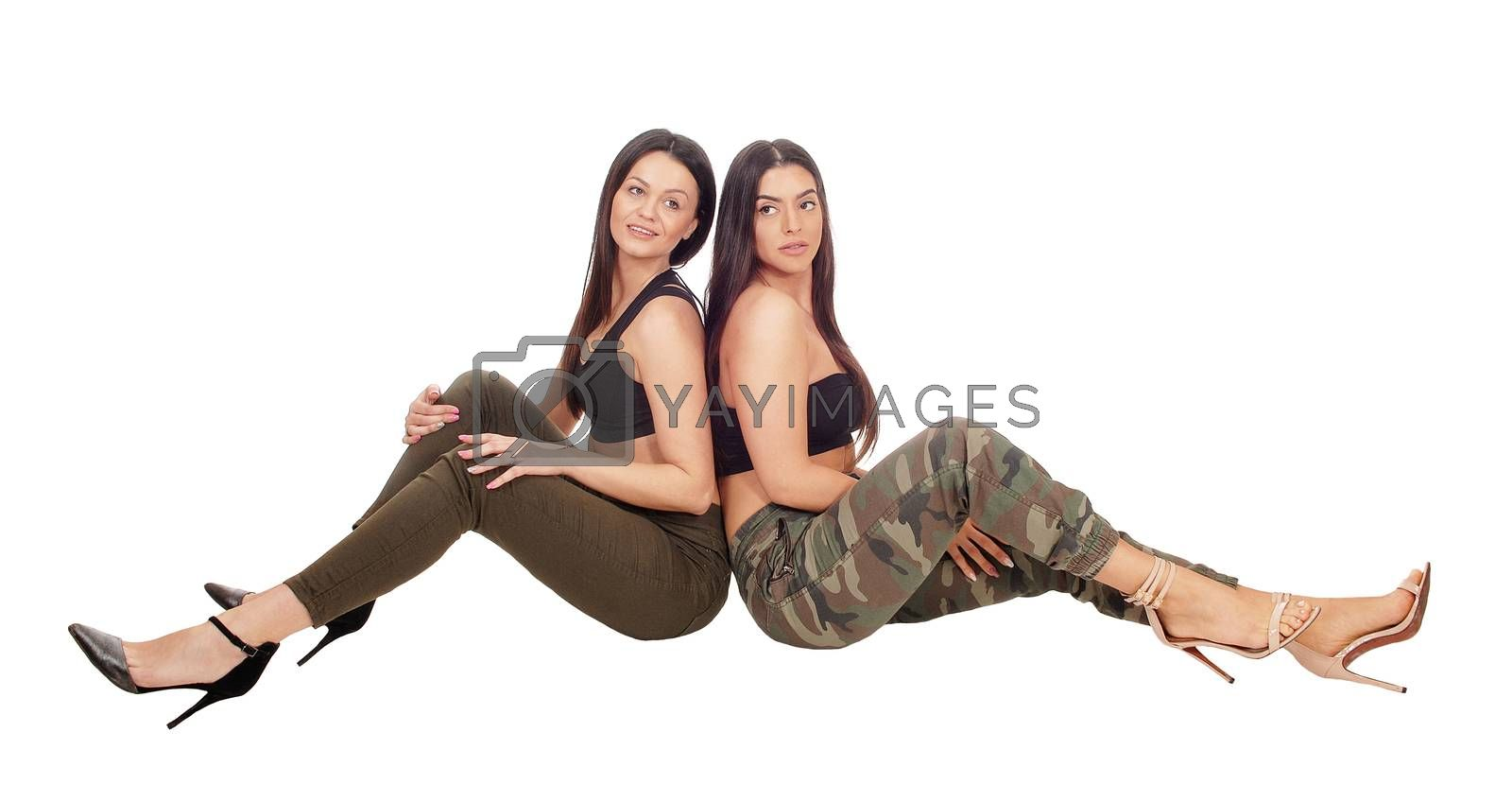 Two beautiful young woman sitting side by side in jeans and heels looking at the camera, isolated for white background