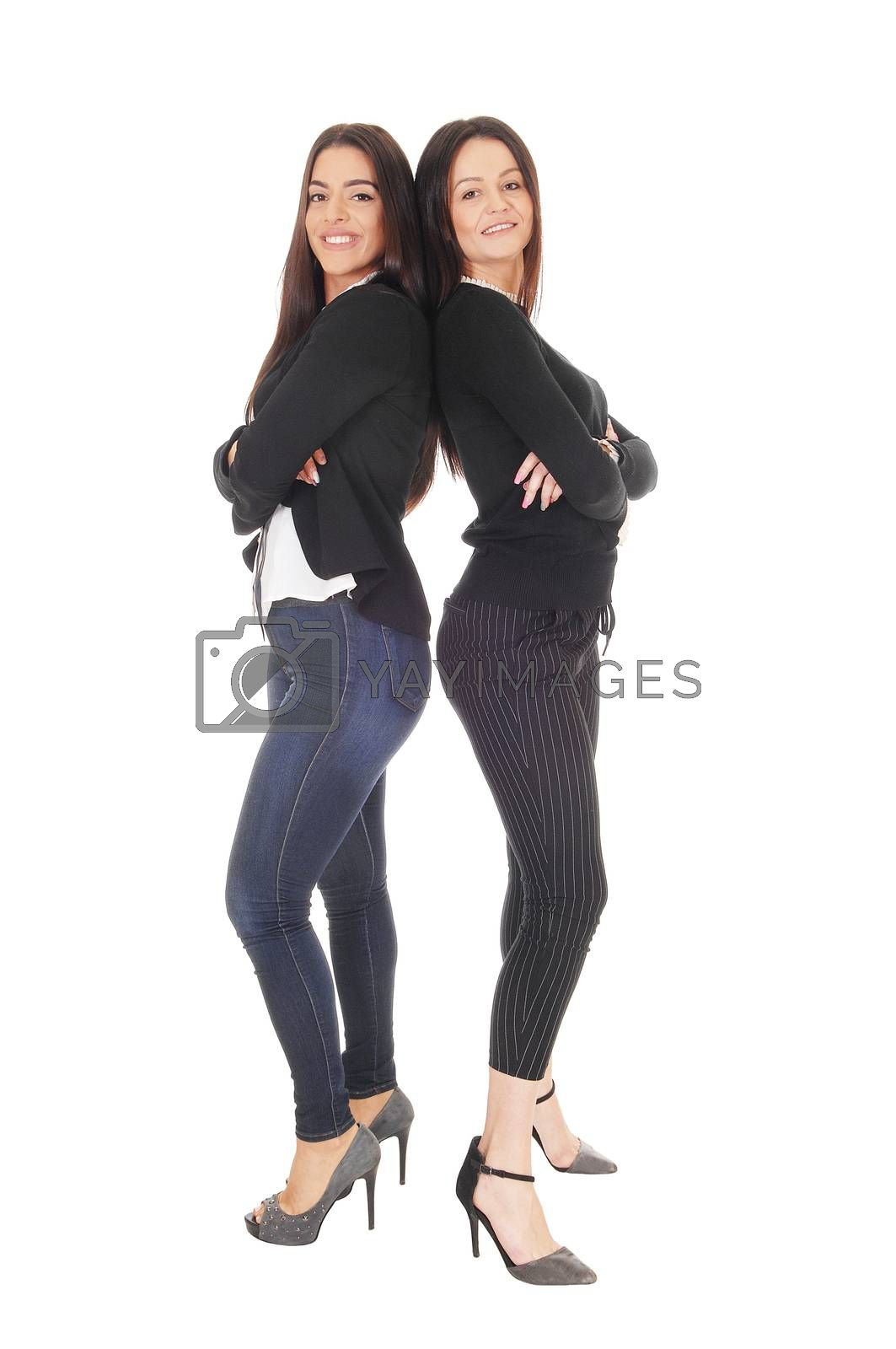 Two beautiful young woman standing back to back in jeans and heels looking at the camera, isolated for white background