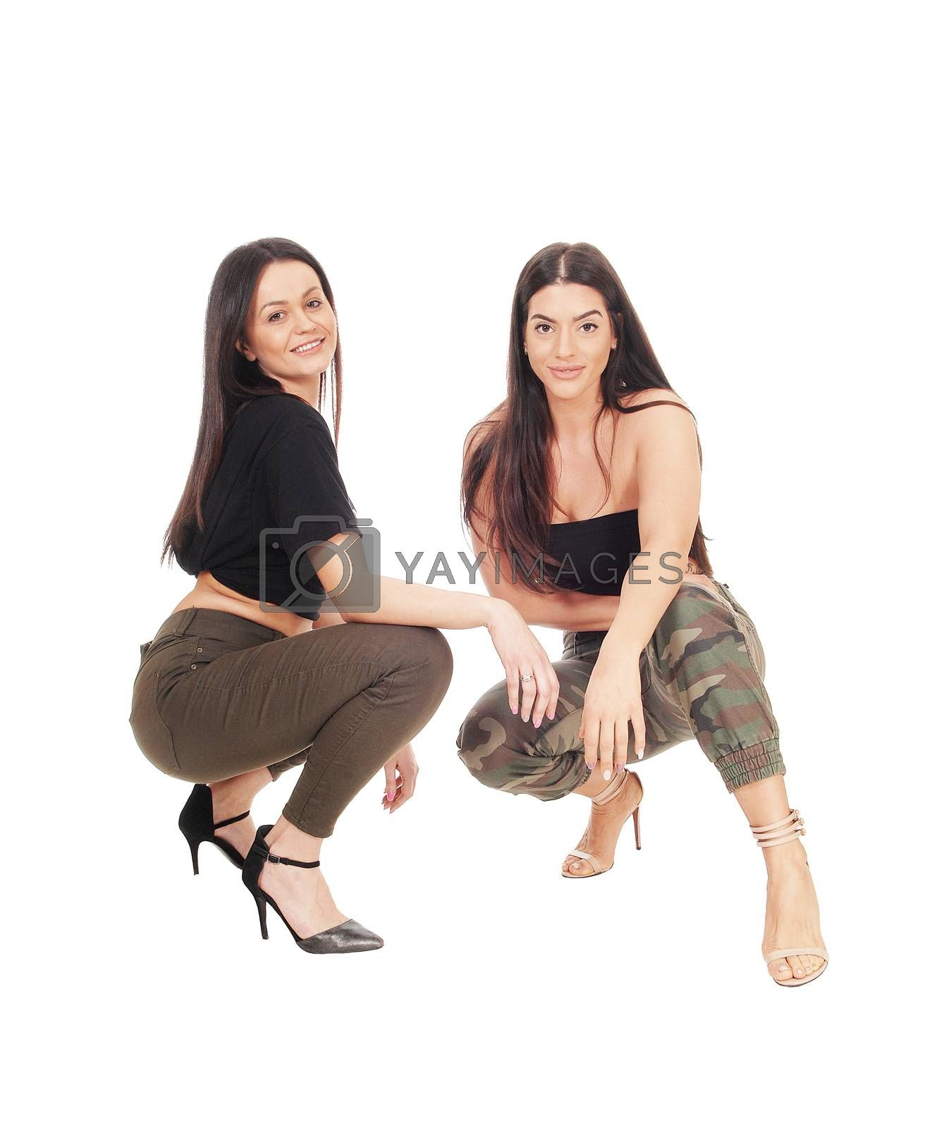 Two beautiful young woman crouching side by side in jeans and heels looking at the camera, isolated for white background