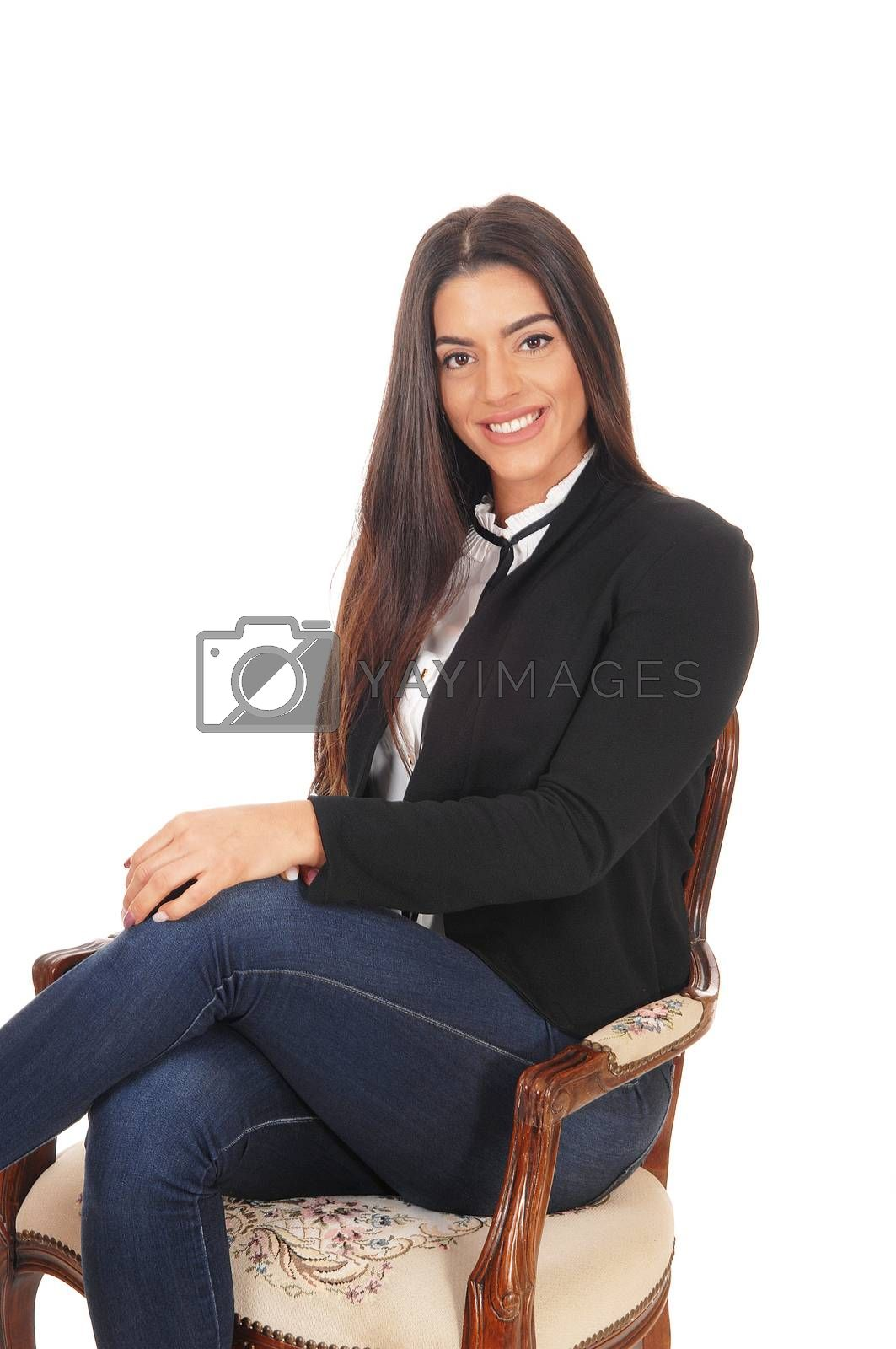 A gorgeous young woman sitting in jeans and a black jacket smiling, isolated for white background