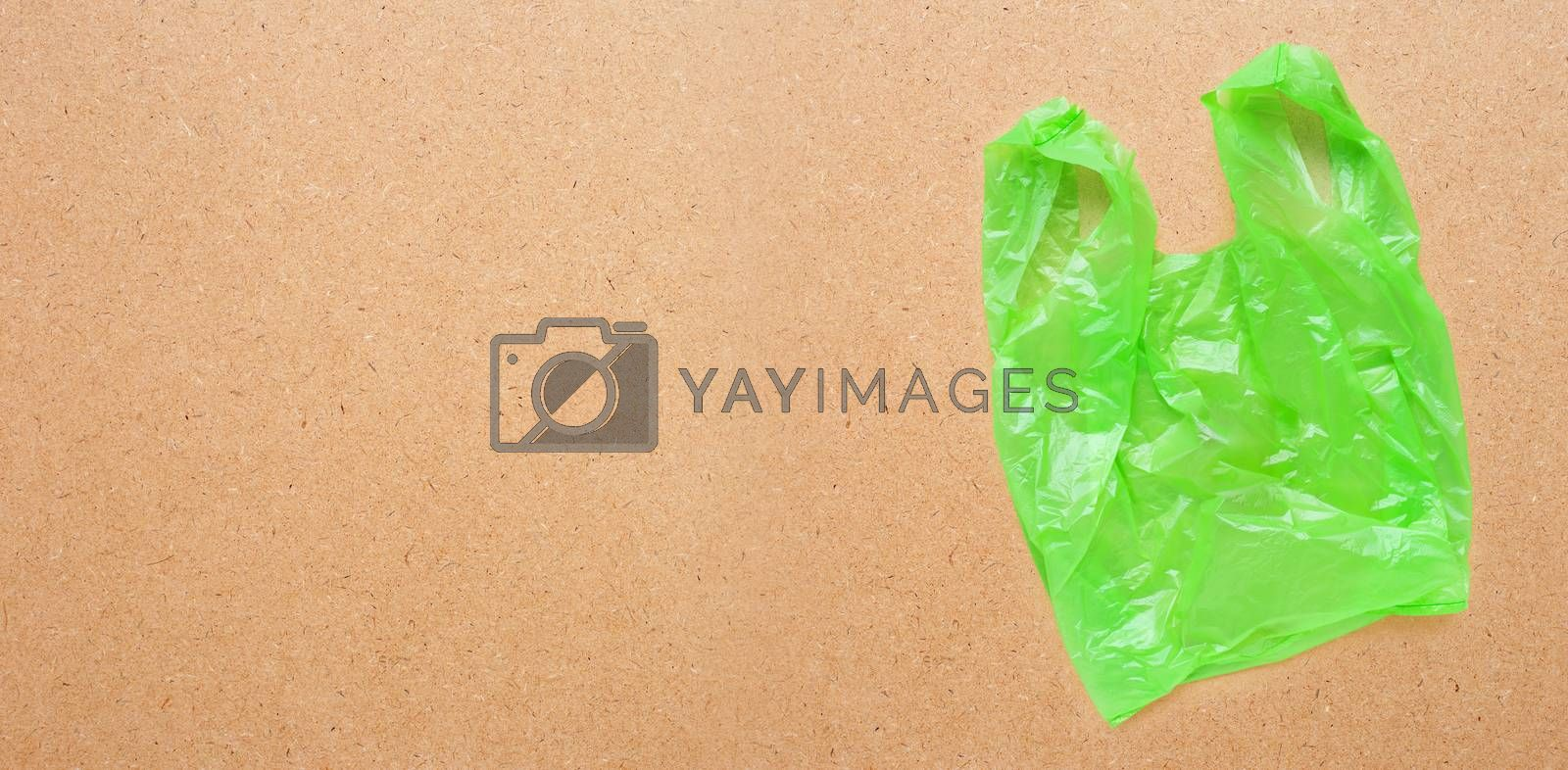 Green plastic bag on plywood background.  Copy space