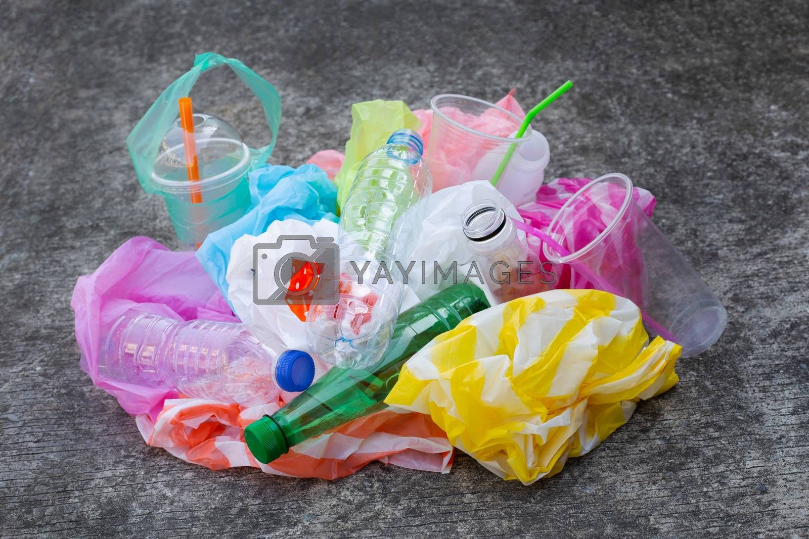 Colorful plastic waste, bags, cups, bottles, straws on cement floor background.