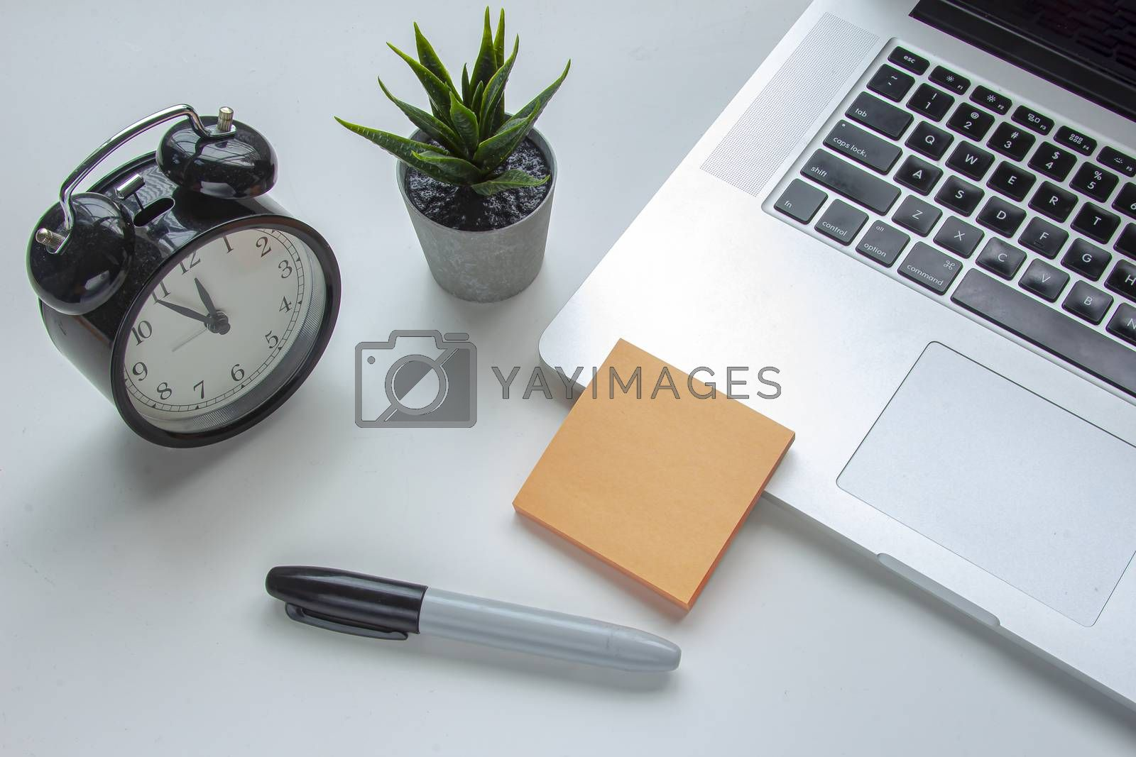 A note an a marker next to a laptop keyboard with a clock and a plant on a white table
