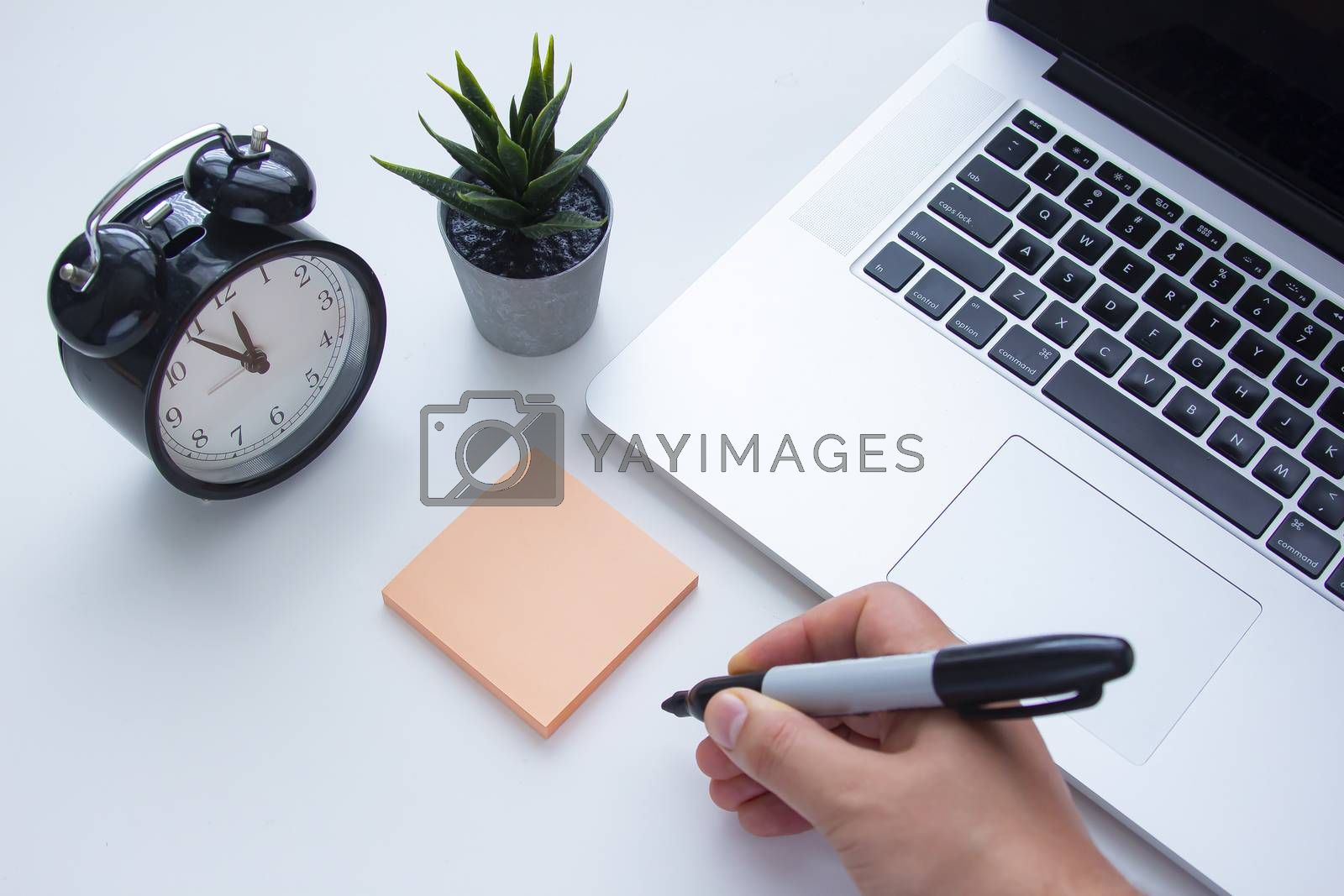 A person about to write a note next to a laptop keyboard with a clock and a plant on a white table