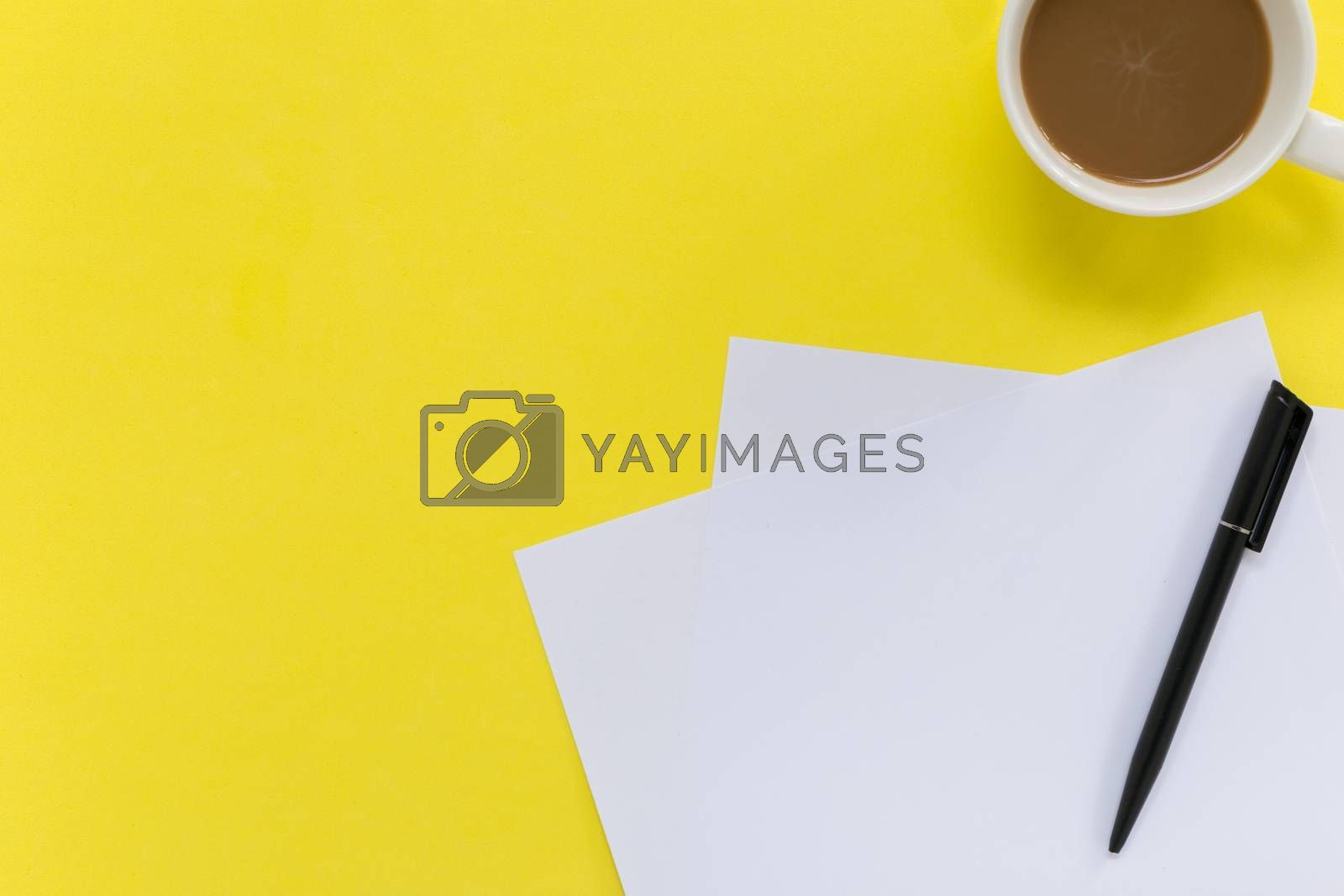 Sheets of white blank paper with pen on yellow background.