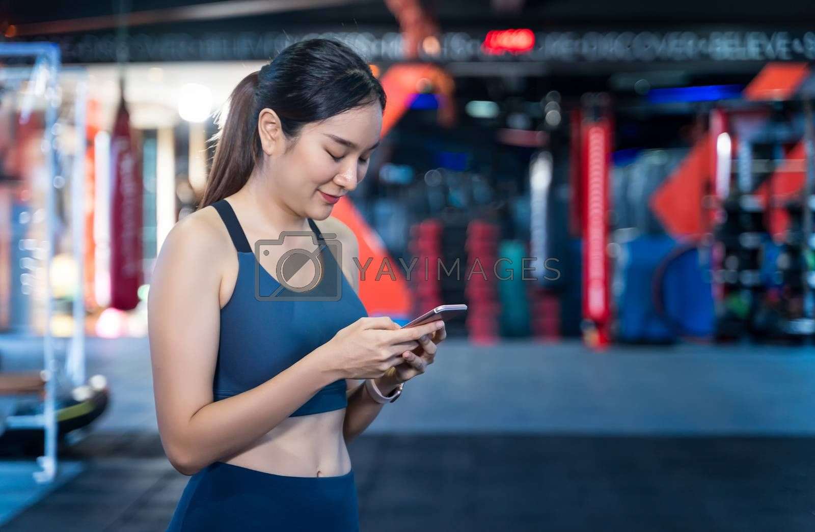 Asian Women are using mobile phones during exercise. She's standing, typing messages or chatting and smiling happily while staying during workouts with blur gym background and copy space
