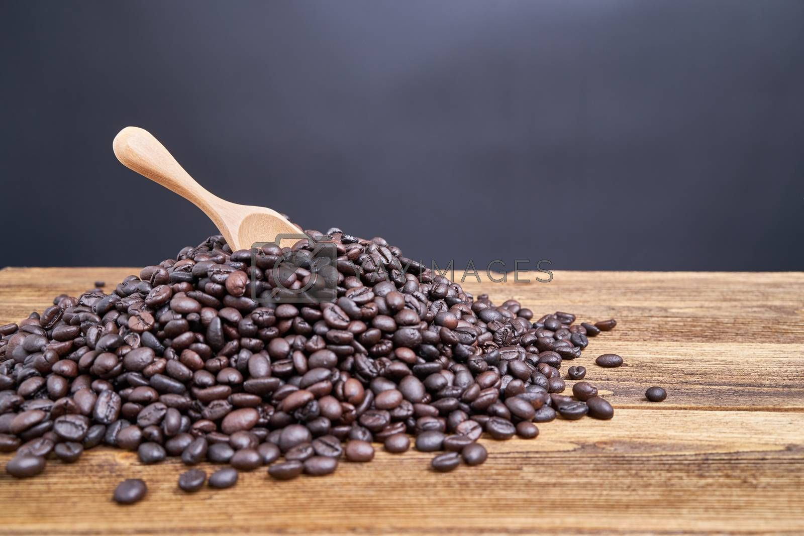 Royalty free image of Close up wood spoon put on pile of coffee bean by eaglesky