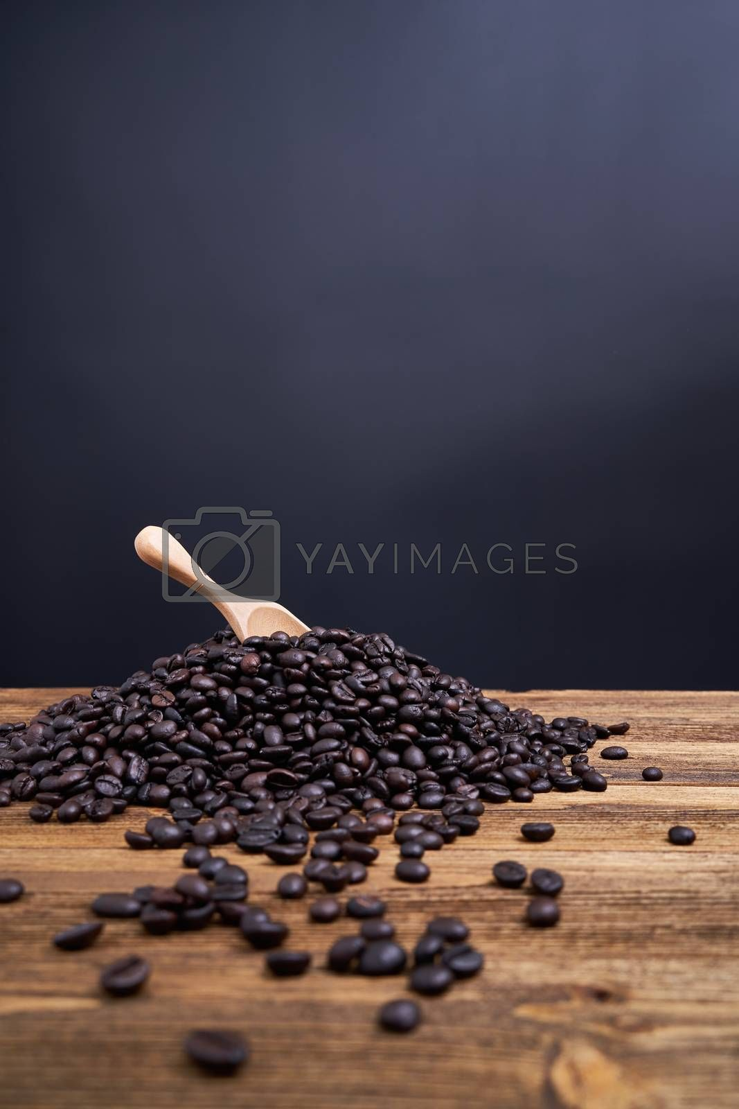 Royalty free image of Wooden spoon put on pile of coffee bean black background by eaglesky
