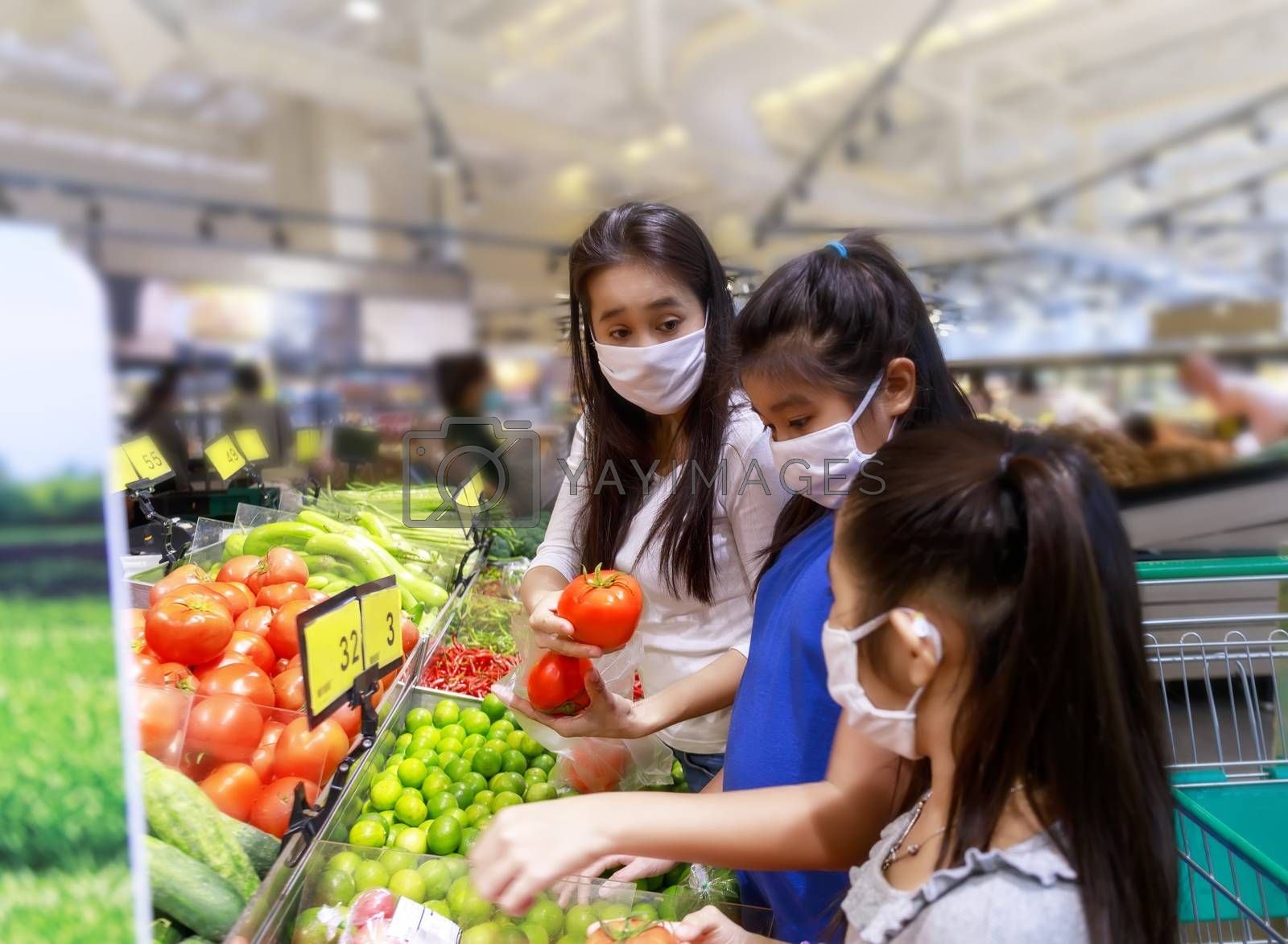 Asian woman with her daughter wear protective face mask in supermarket departmentstore. Mom ฟืก daughter looking grocery to buy  ดruit and vegetable. Womenhold red tomatos. Soft focus and selective Women. New normal after covid-19. Family concept.