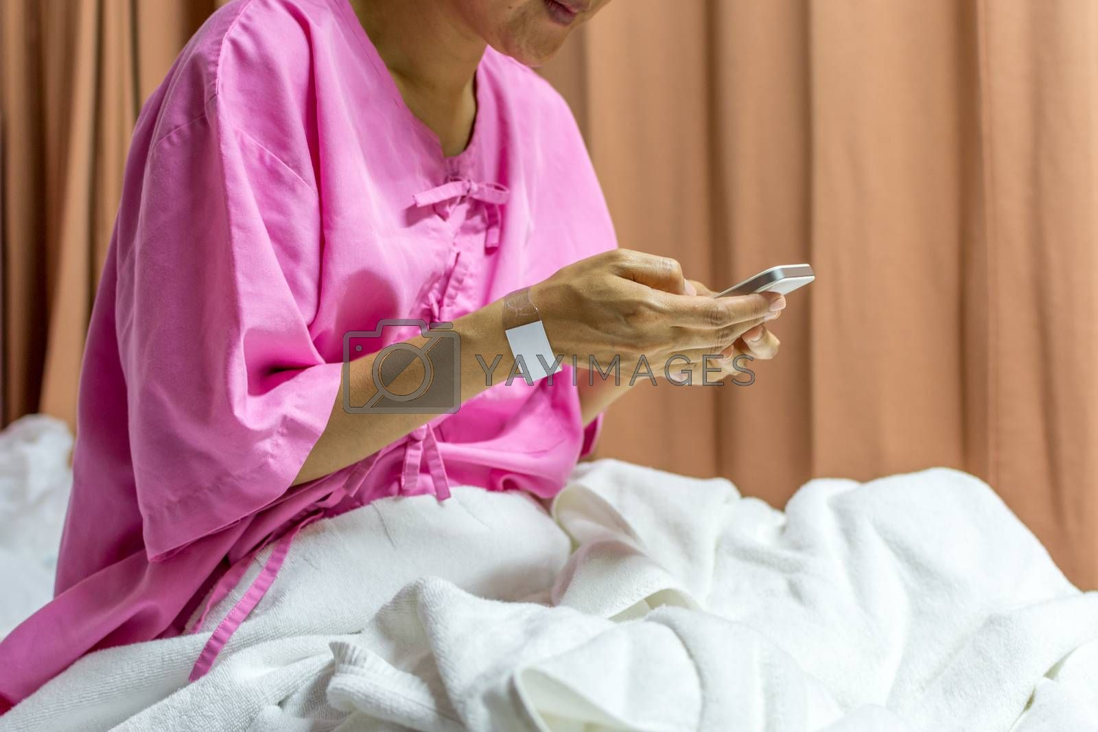 Patient asian woman with adhesive plaster on hand using smartphone for internet communication on patient bed in the hospital