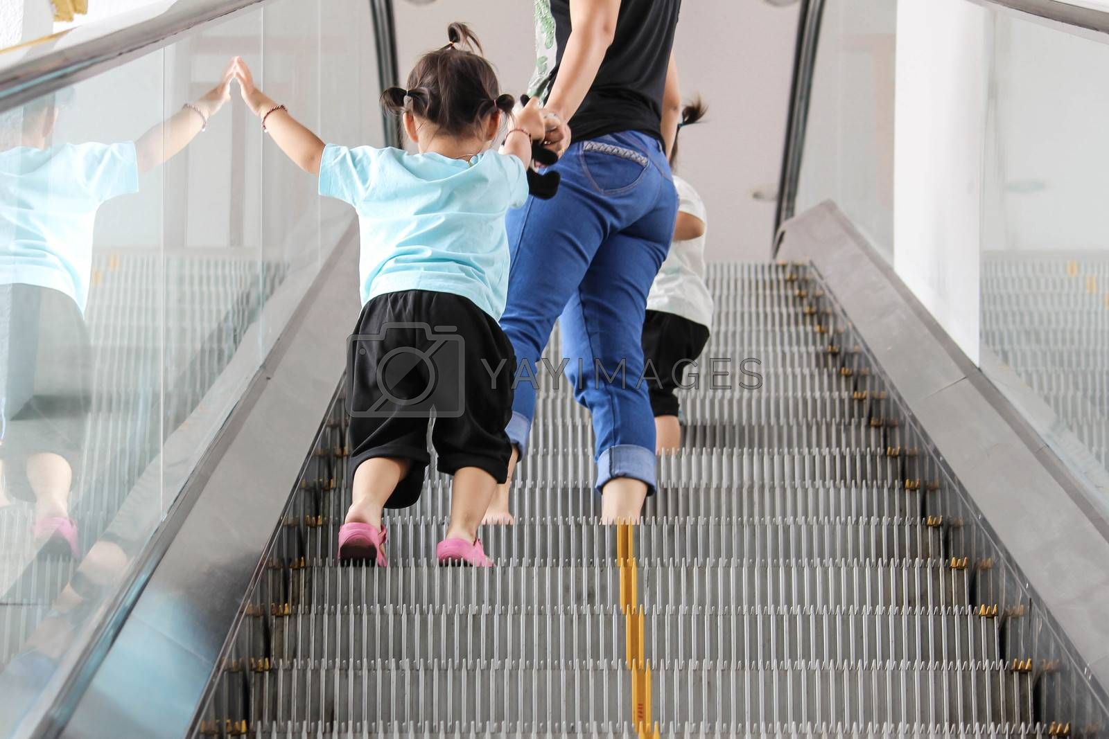Back view of mother and child walking up together on broken escalator background. by TEERASAK