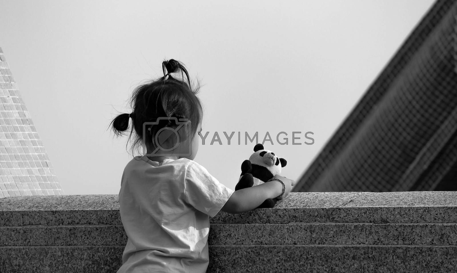 Asian little girl standing on the balcony for a view in the garden with favorite bear. View from the back by TEERASAK