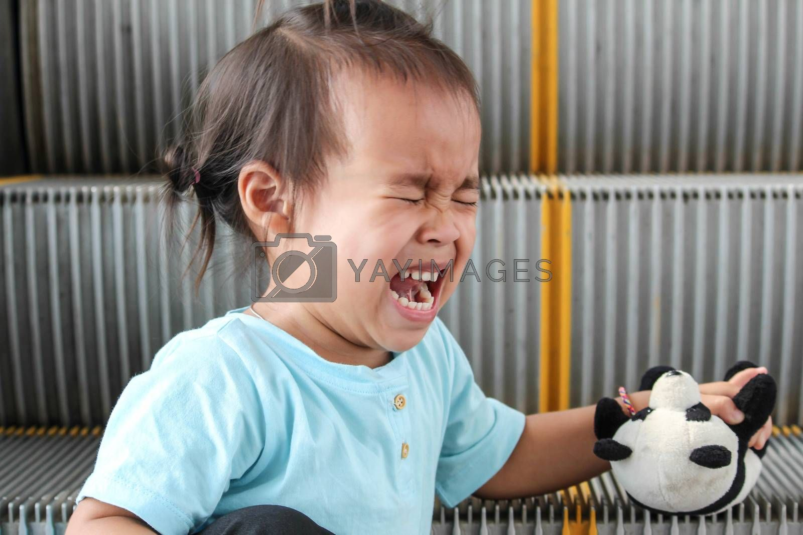 Child crying while falling on broken escalator background. by TEERASAK