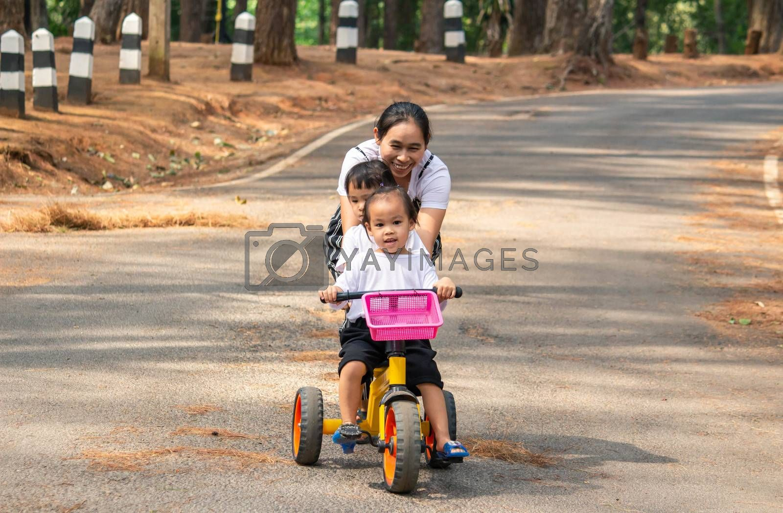 Asian young mother holding bicycle to her daughters, that riding a bicycle with her sister on the road in the garden. by TEERASAK