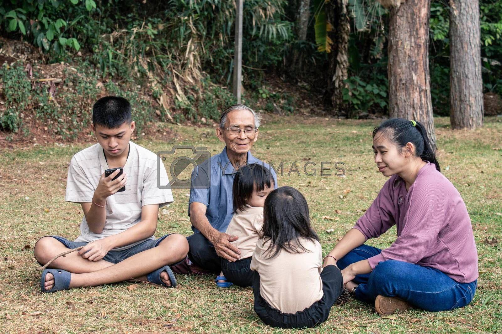 Asian family sitting on grasses ground in the garden for relaxation in summer day. by TEERASAK
