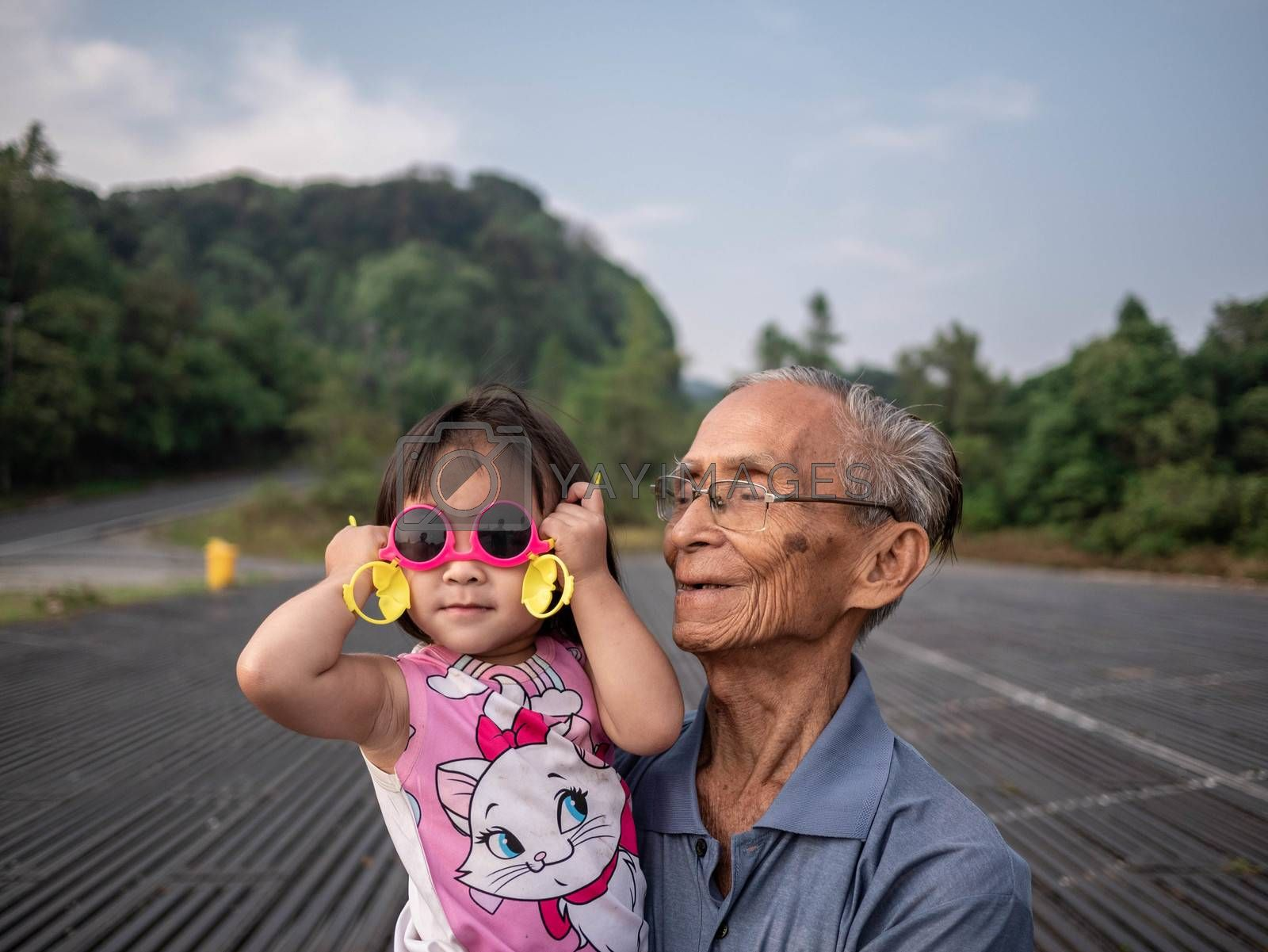 Asian grandfather carrying grandchild while her wearing pink glasses and smile.