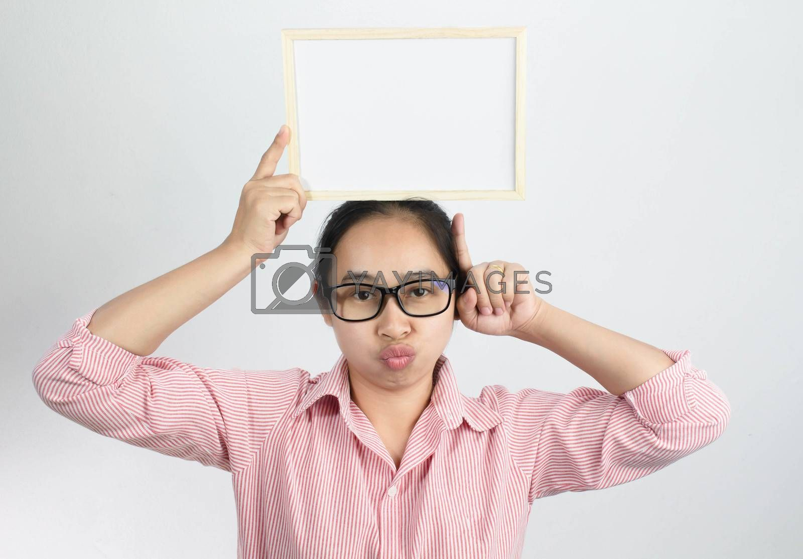 Happy face Asian woman holding blank white board on her head and show finger pointing isolated on a white background. Copy Placed or space for text. by TEERASAK