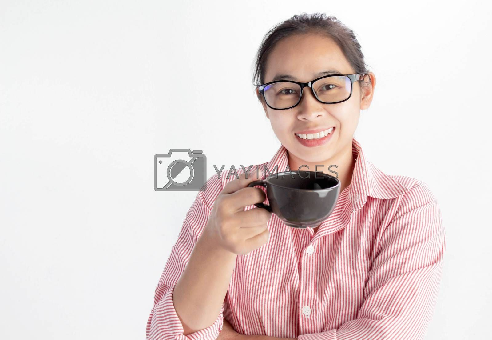Close up portrait of confident Asian woman, wearing glasses and holding coffee cup, looking camera and smile, standing over white background with copy space. by TEERASAK