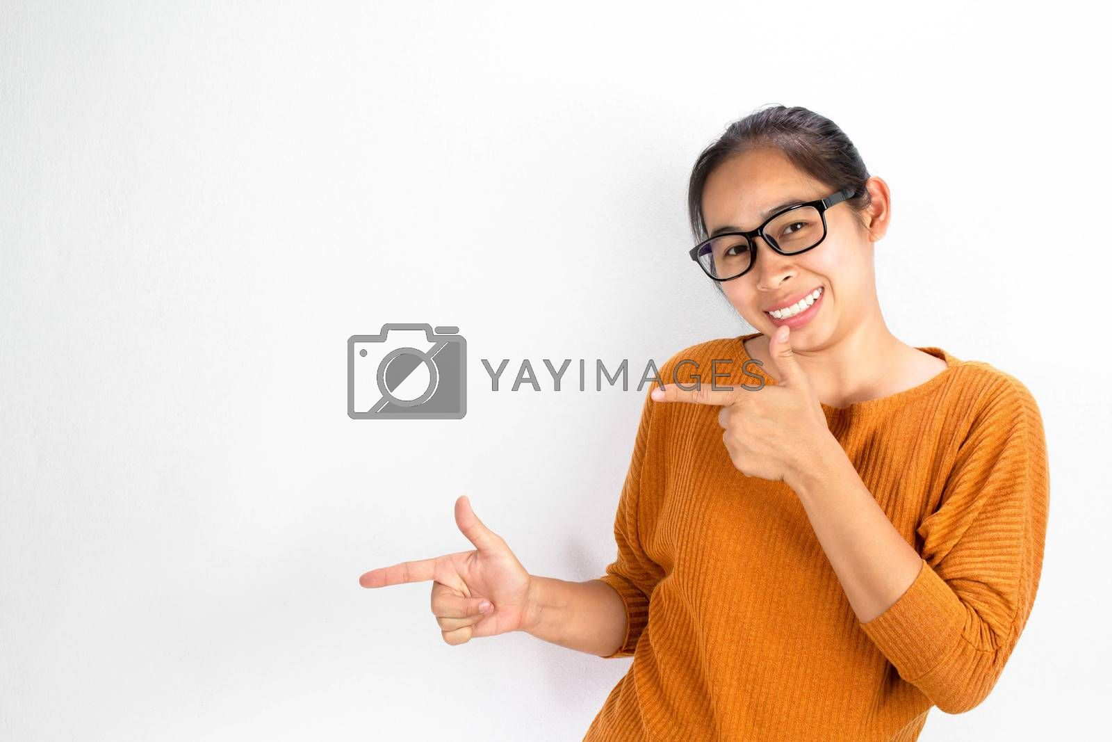 Asian woman wearing orange shirt and eyeglasses isolated on white background smiling and looking at the camera pointing with two hands and fingers to the side. by TEERASAK