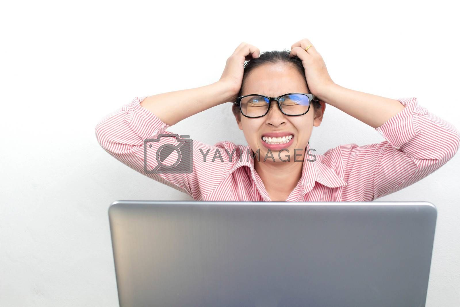 Close up portrait of stressed Asian woman, wearing glasses, looking tablet with seriously face and have headach symtom, sitting over white background with copy space. by TEERASAK