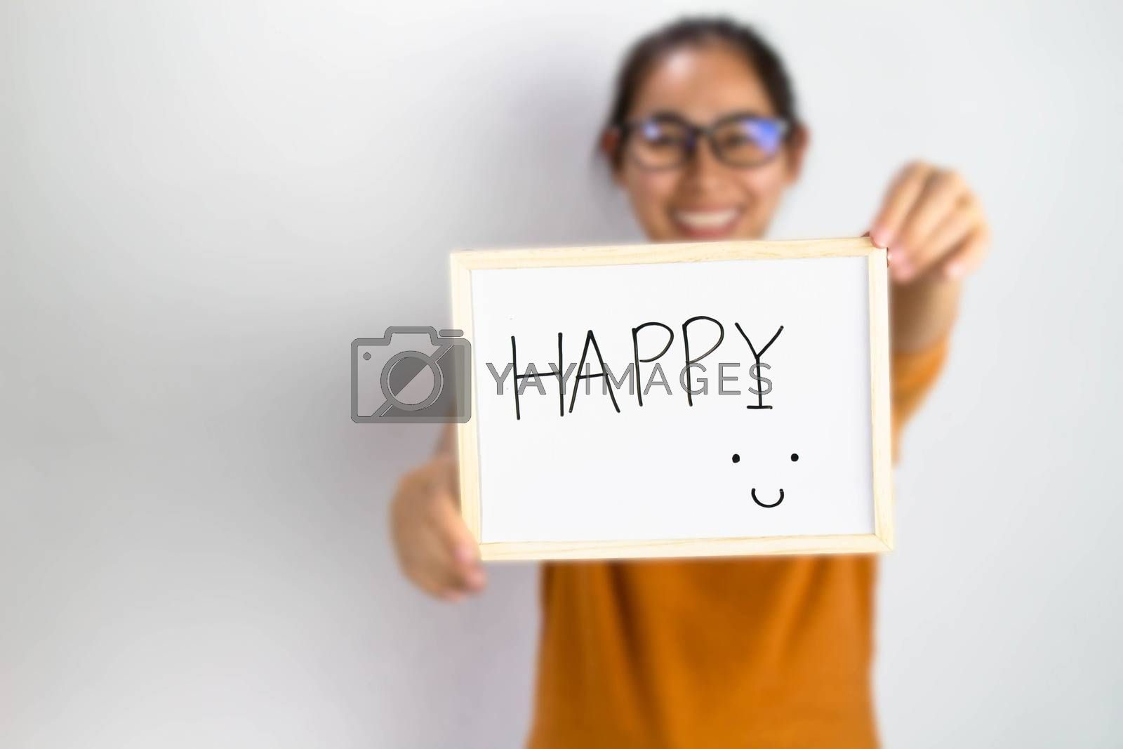 Happy Asian woman holding a Happy sign writing on whiteboard with handwriting. Isolated on white background. by TEERASAK