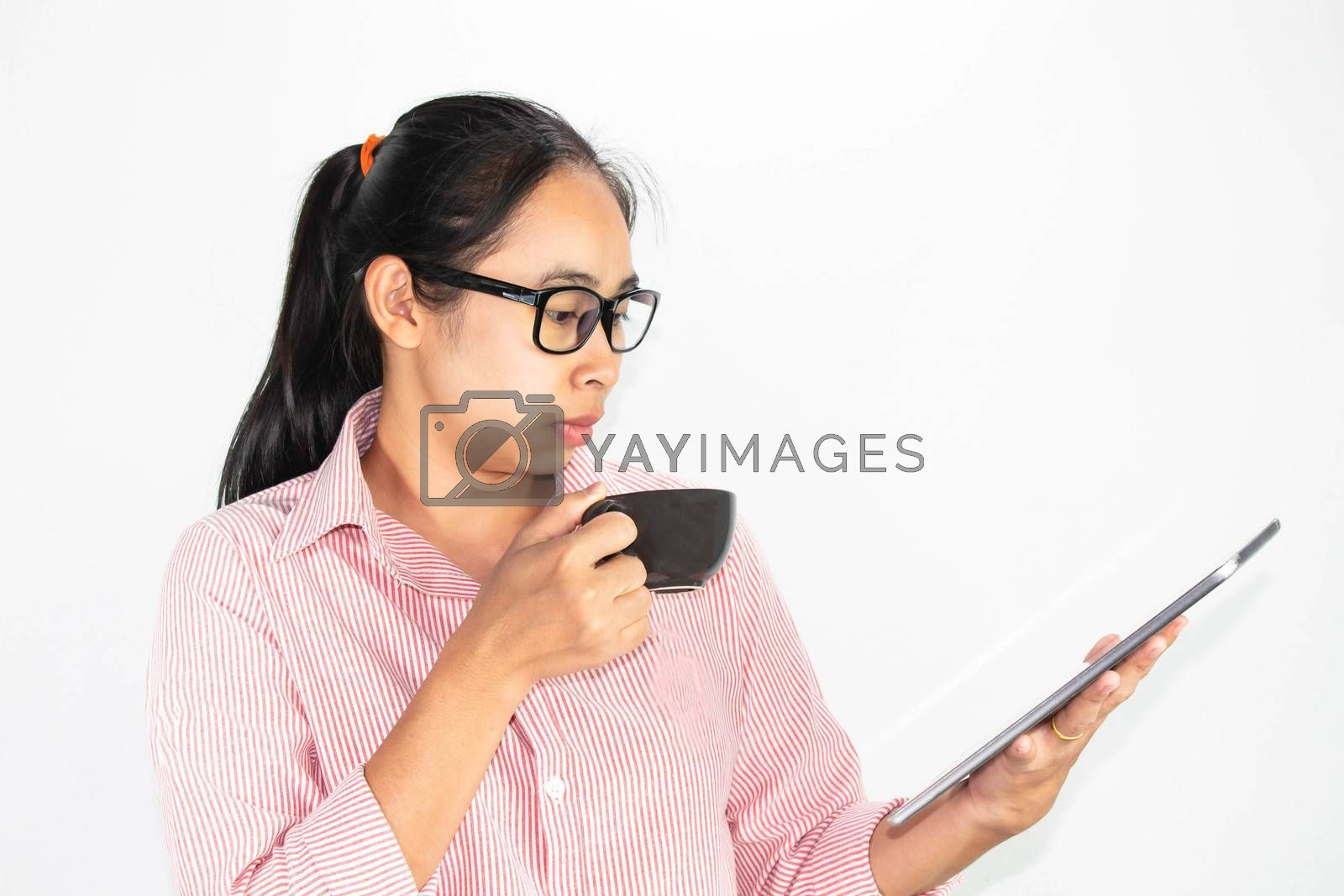 Close up portrait of confident Asian woman, wearing glasses and holding coffee cup, looking tablet with looking seriously face, standing over white background with copy space. by TEERASAK