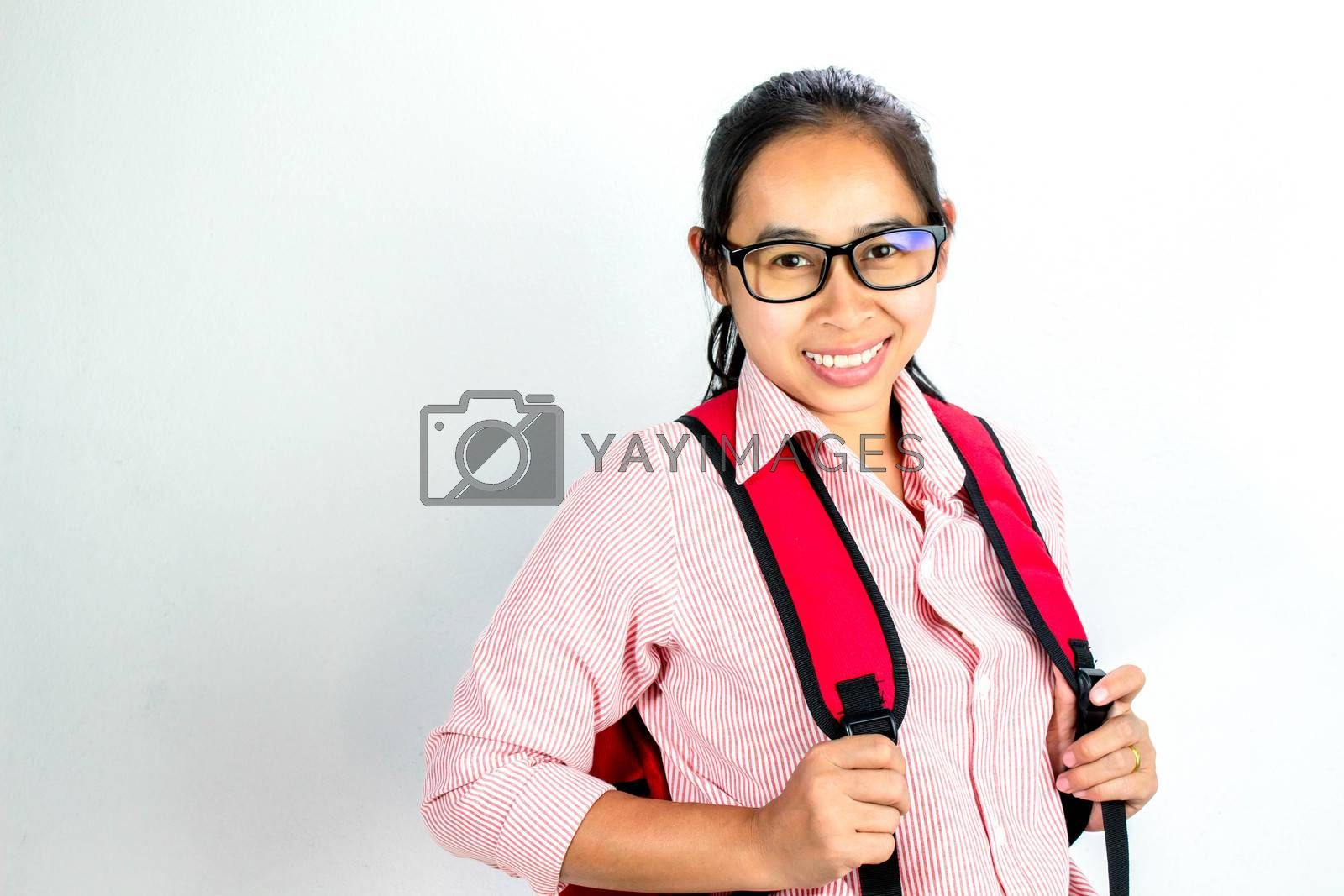 Portrait of Asian woman smiling face, wearing glasses with a red bagpack, standing over white background with copy space. by TEERASAK