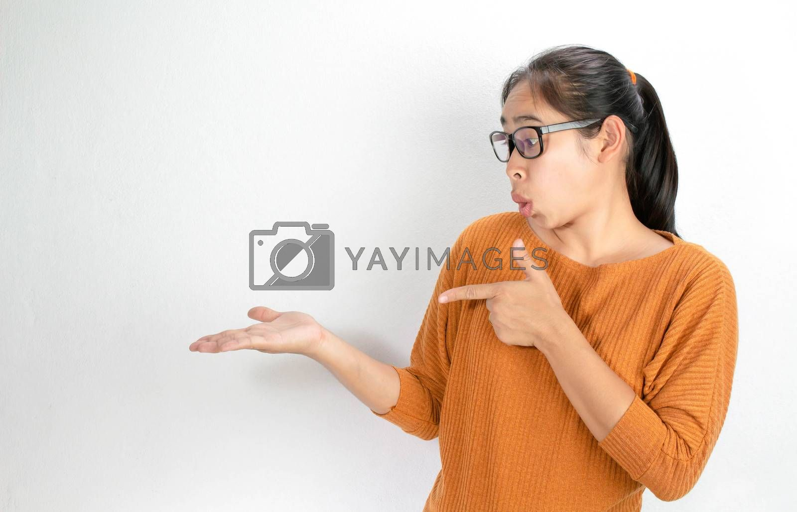 Asian woman wearing orange shirt and eyeglasses holding copy space on the palm and pointing on it while have shocked face. Isolated on white background by TEERASAK