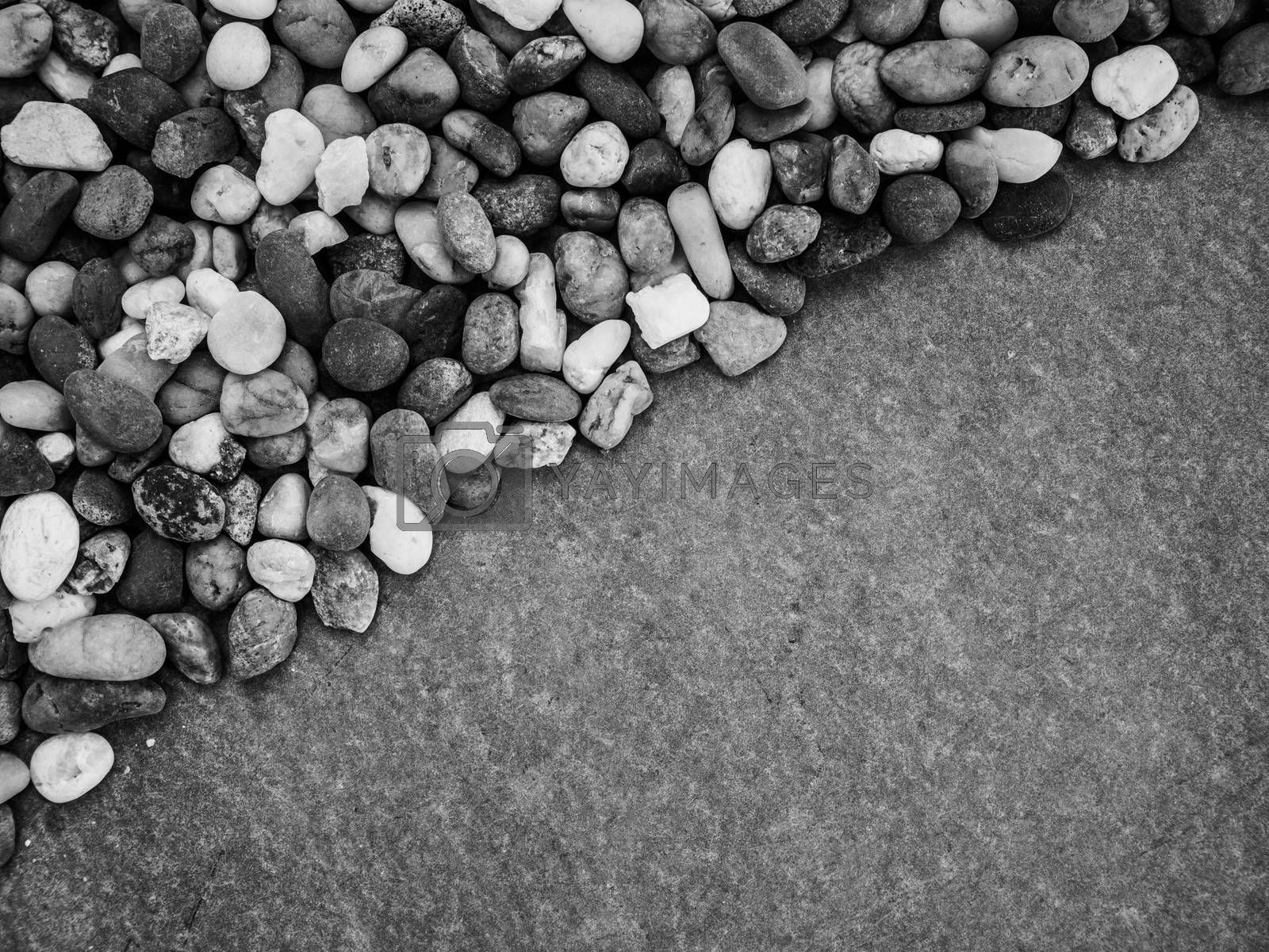 Pebbles pattern or small stones background in garden with copy space for your text. Black and white picture.