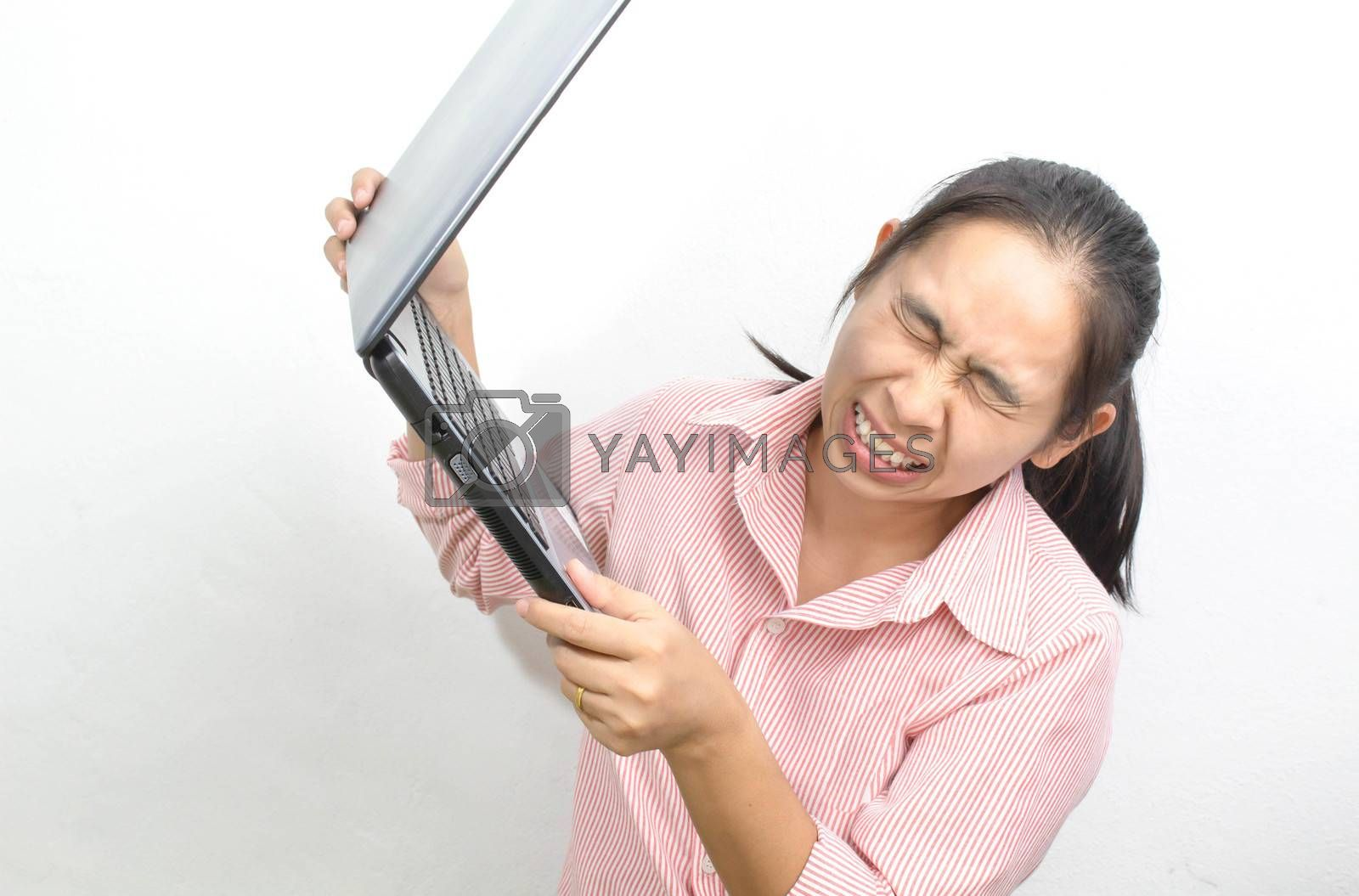 Young angry Asian woman open mouth screaming raising the laptop up to throw it away isolated on a white background. by TEERASAK