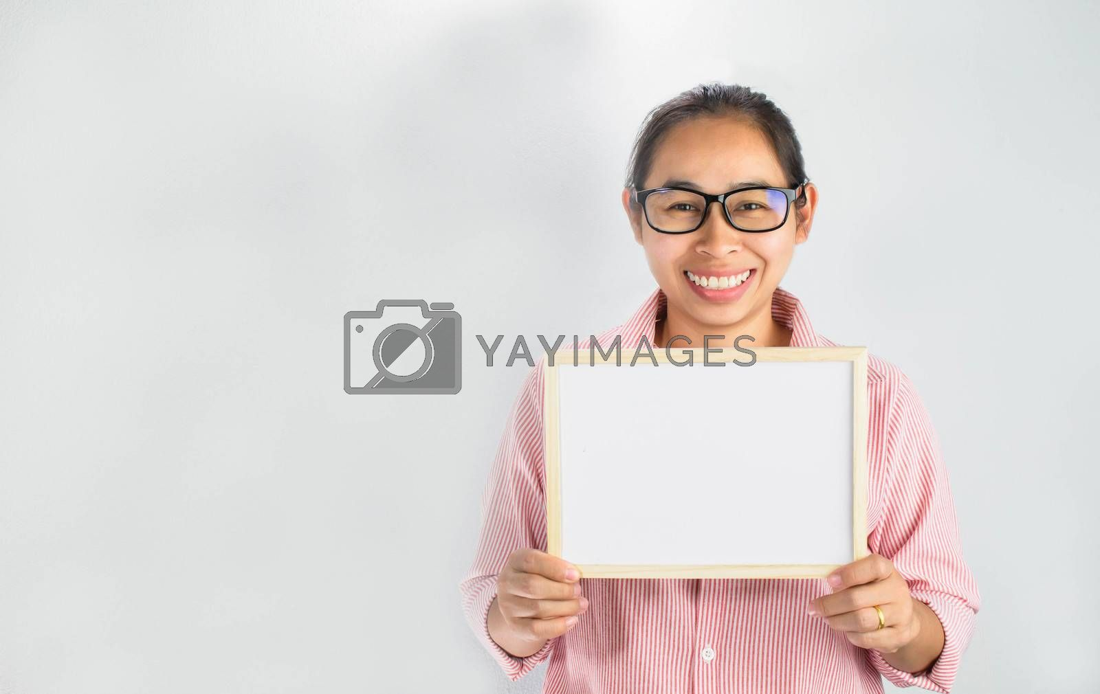Happy face Asian woman holding blank white board for copy placed isolated on a white background. by TEERASAK