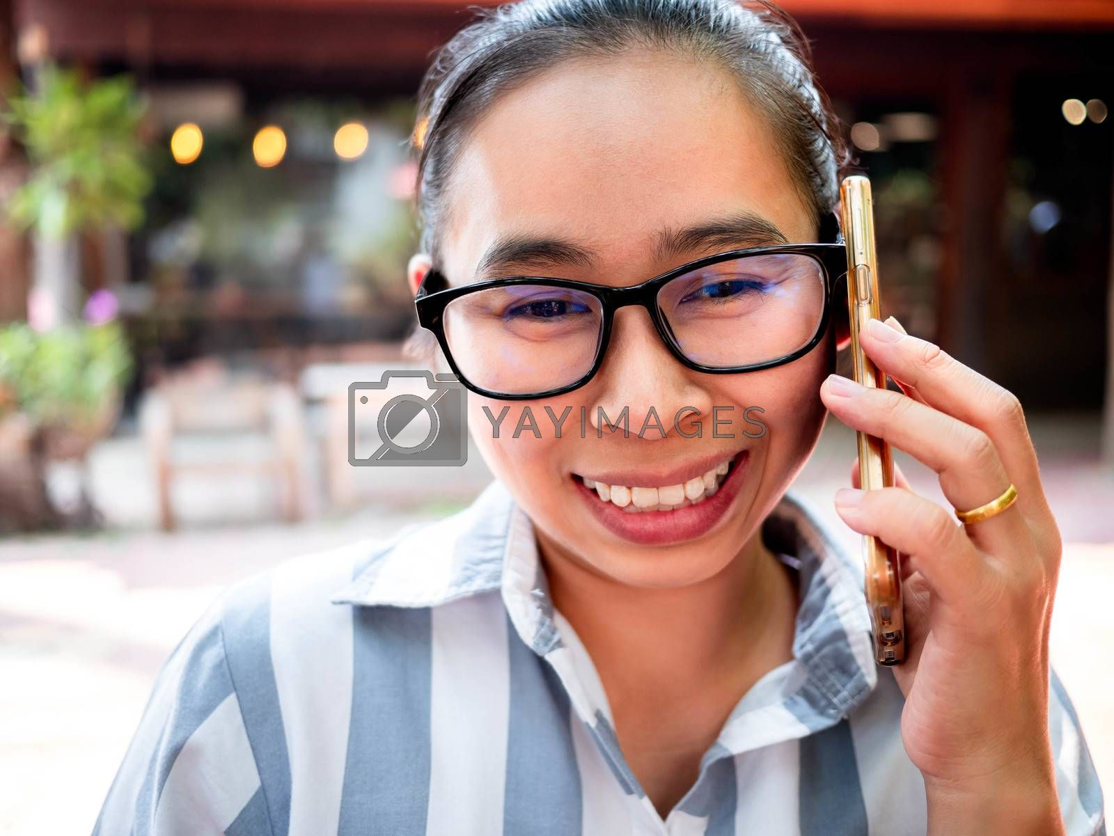 Cheerful Asian young woman talking on the phone at coffee cafe, smiling face. by TEERASAK