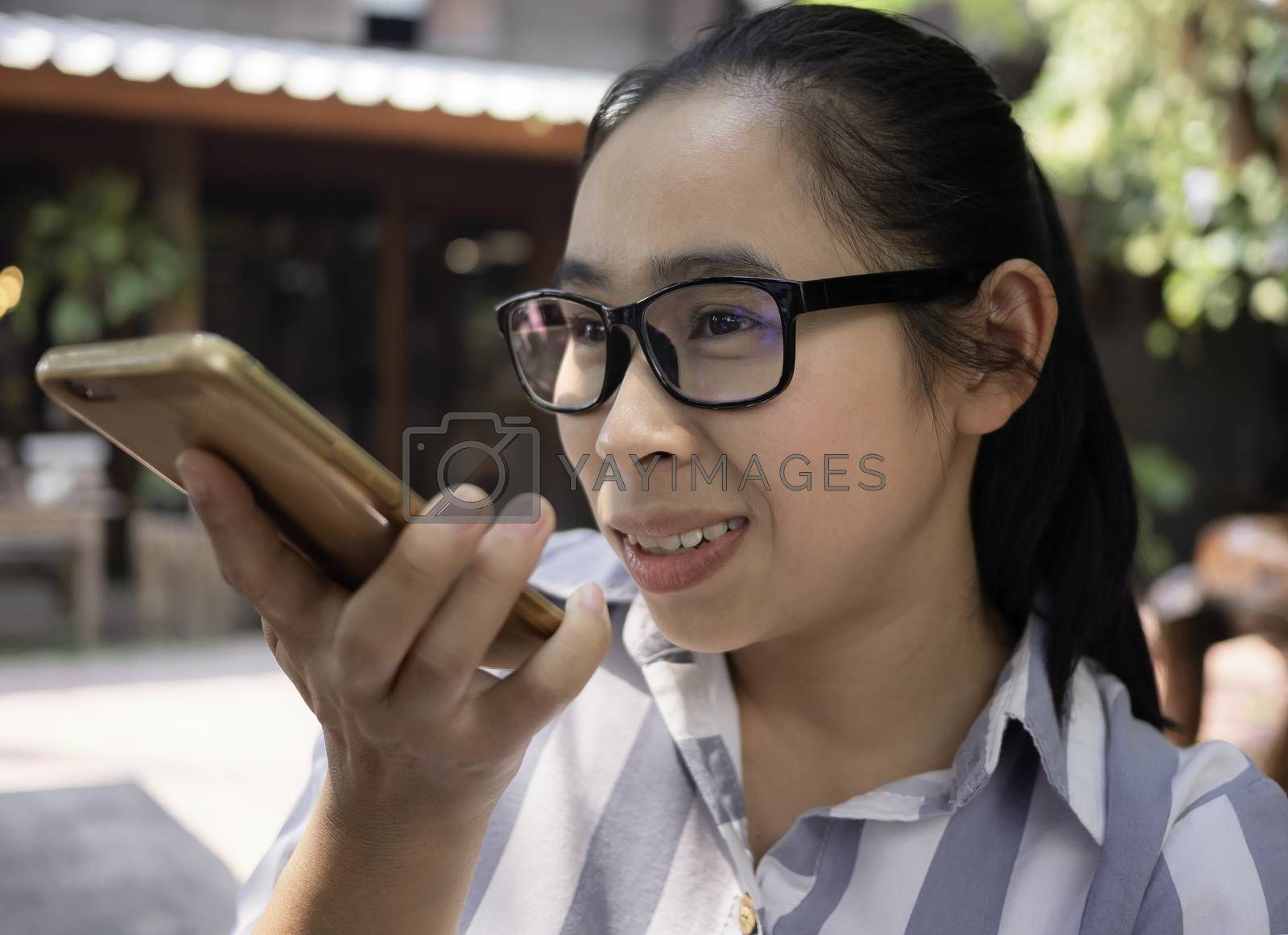 Joyful Asian young woman talk on the speaker phone with smile face in coffee cafe. by TEERASAK