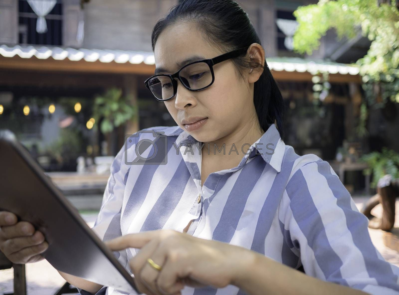 Confidenced business Asian young woman talking on the phone at coffee cafe, Serious face. by TEERASAK