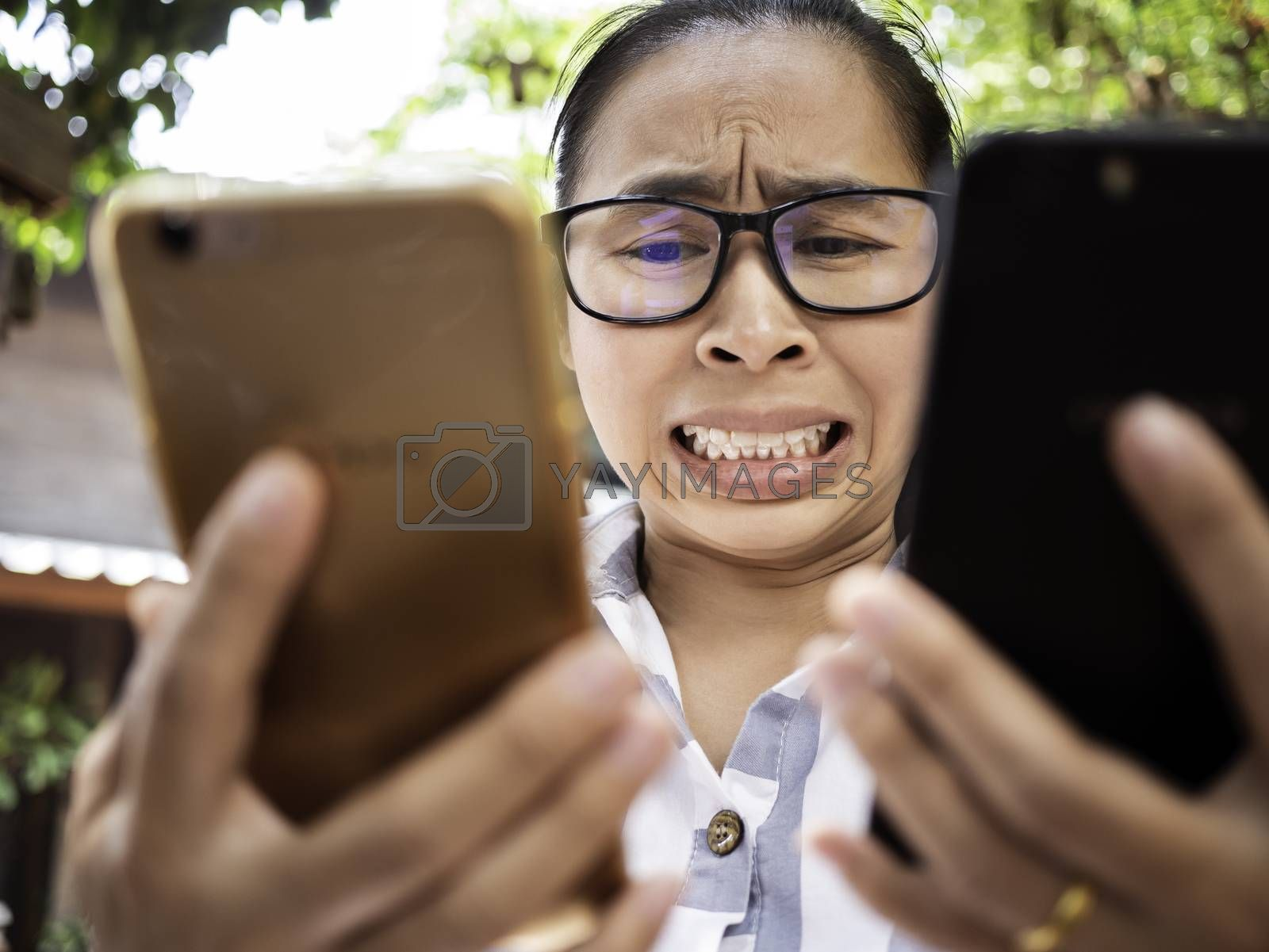 Business Asian young woman holding 2 smartphone do busy with work, Unhappy and worry face. by TEERASAK