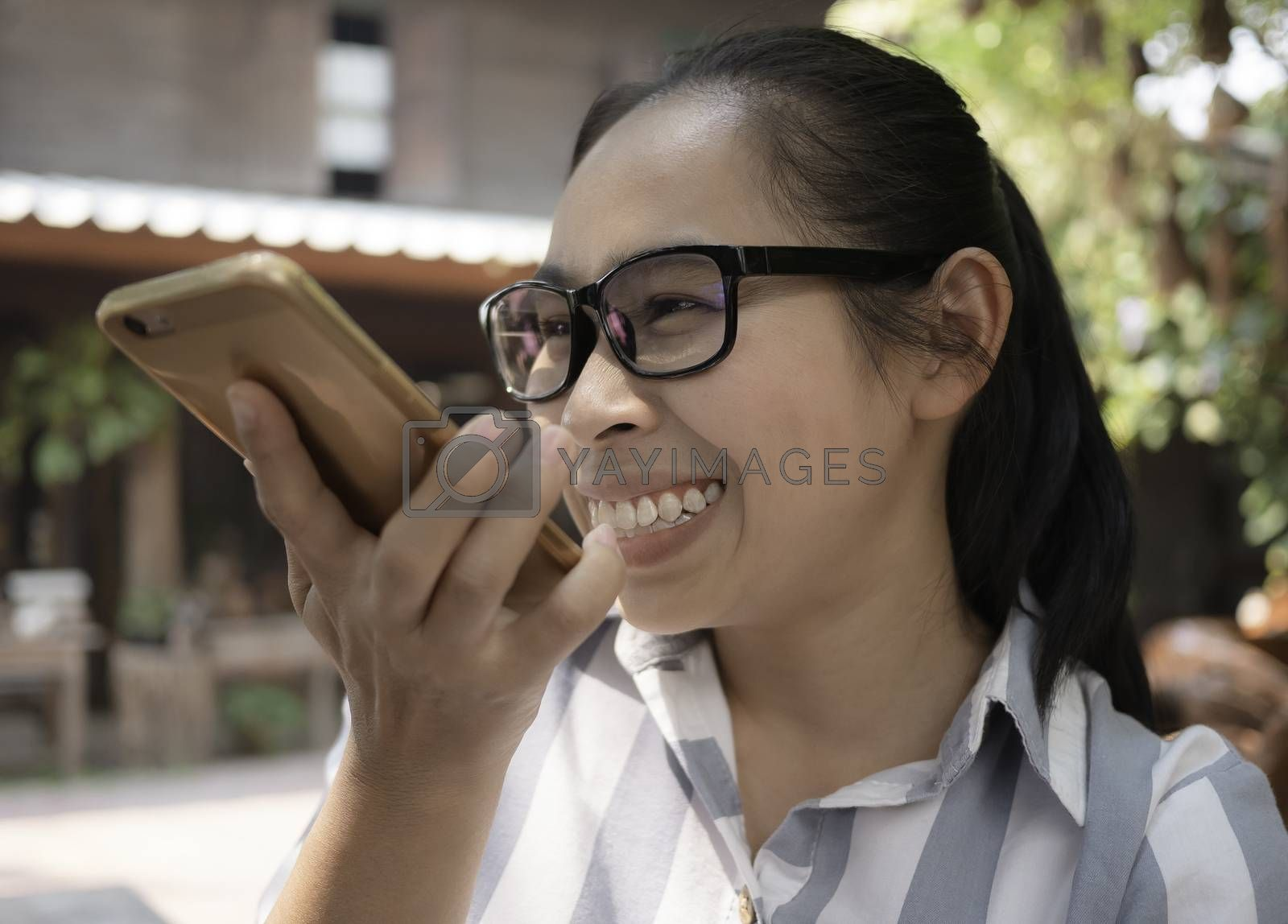 Joyful Asian young woman talk on the speaker phone with smile face in coffee cafe.