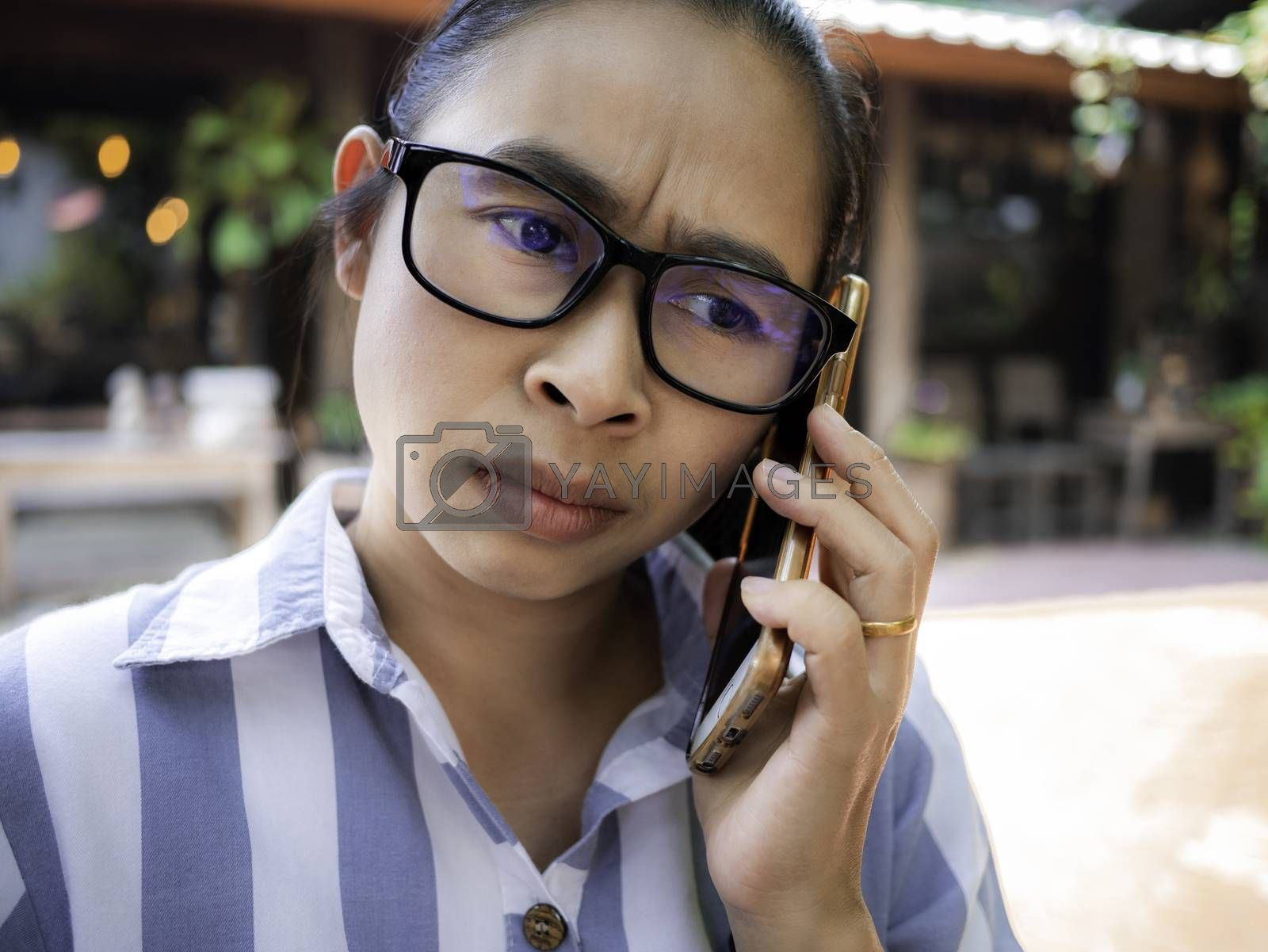 Stressed Asian young woman talking on the phone at coffee cafe.