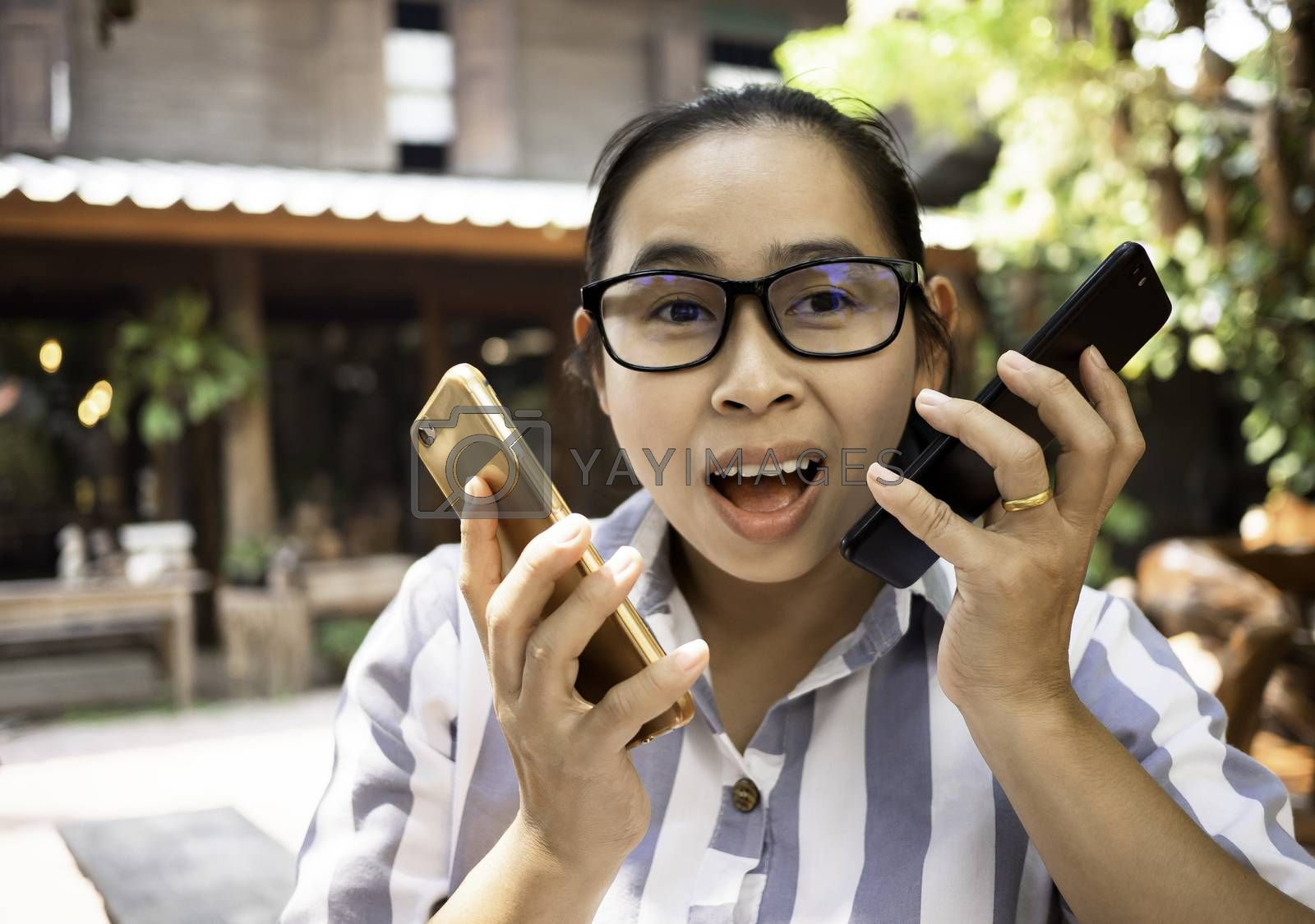 Business Asian young woman holding smartphone do busy with work while talking on the phone simultaneously at coffee cafe. by TEERASAK