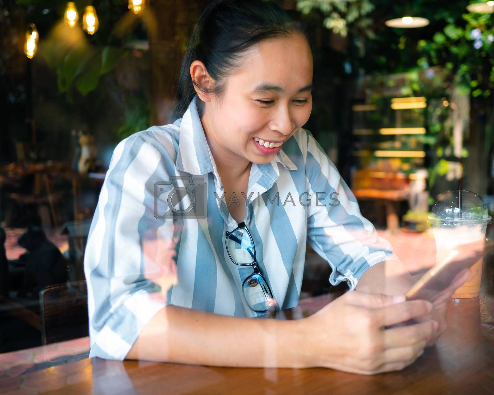 Cheerful business Asian young woman sitting on wooden chair and using smartphone at coffee cafe on weekend, happy and smiley face. by TEERASAK