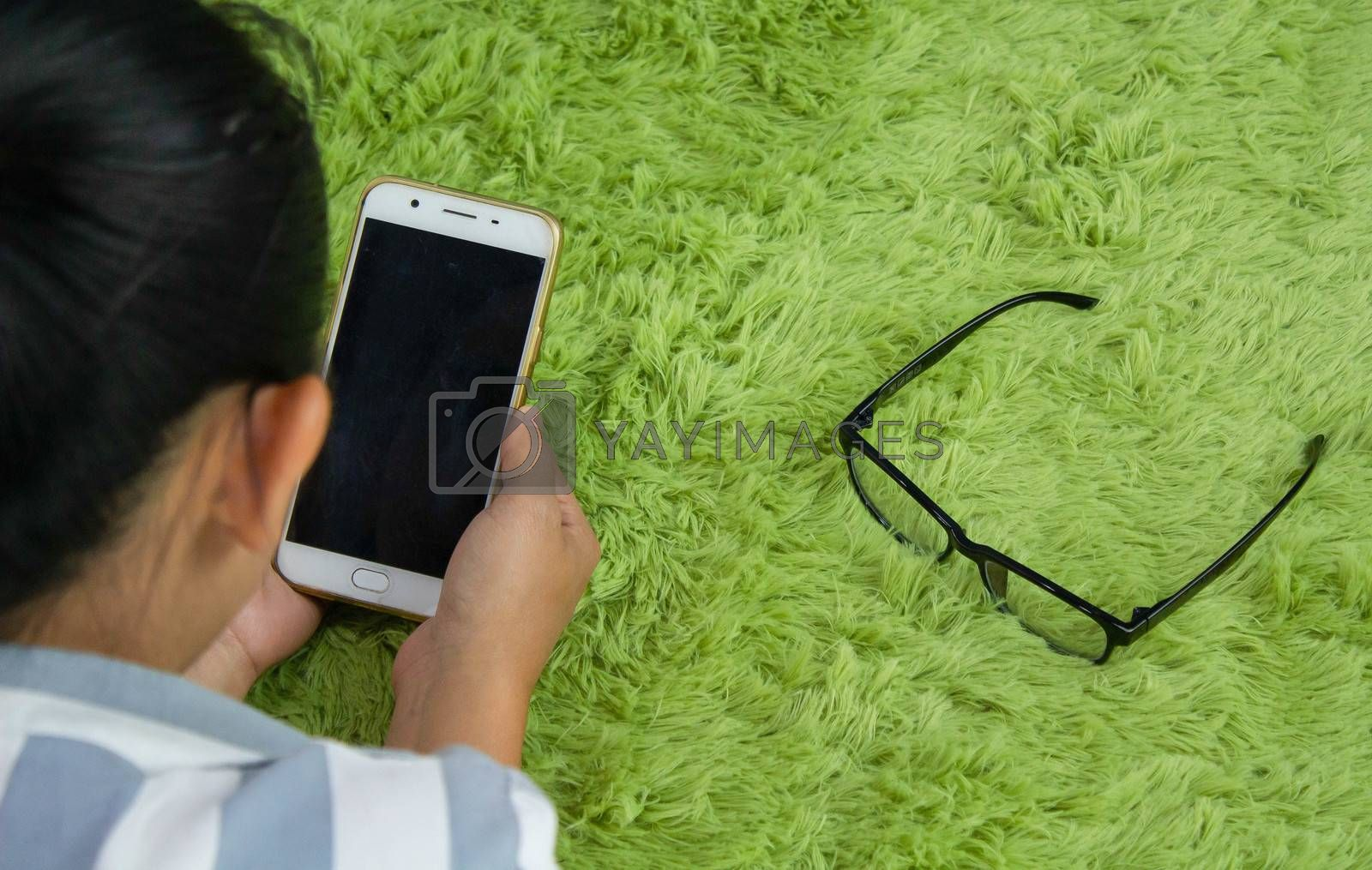 Close up of Asian young woman hand using a smartphone while lying down on green furry carpet at home.
