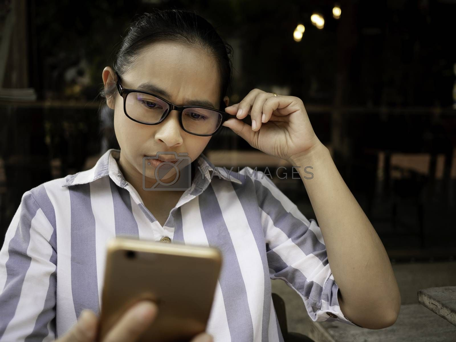 Stressed Asian women sitting on wooden chair with smartphone. She have eye pain from looking at the smartphone for too long. Health and medical concept.